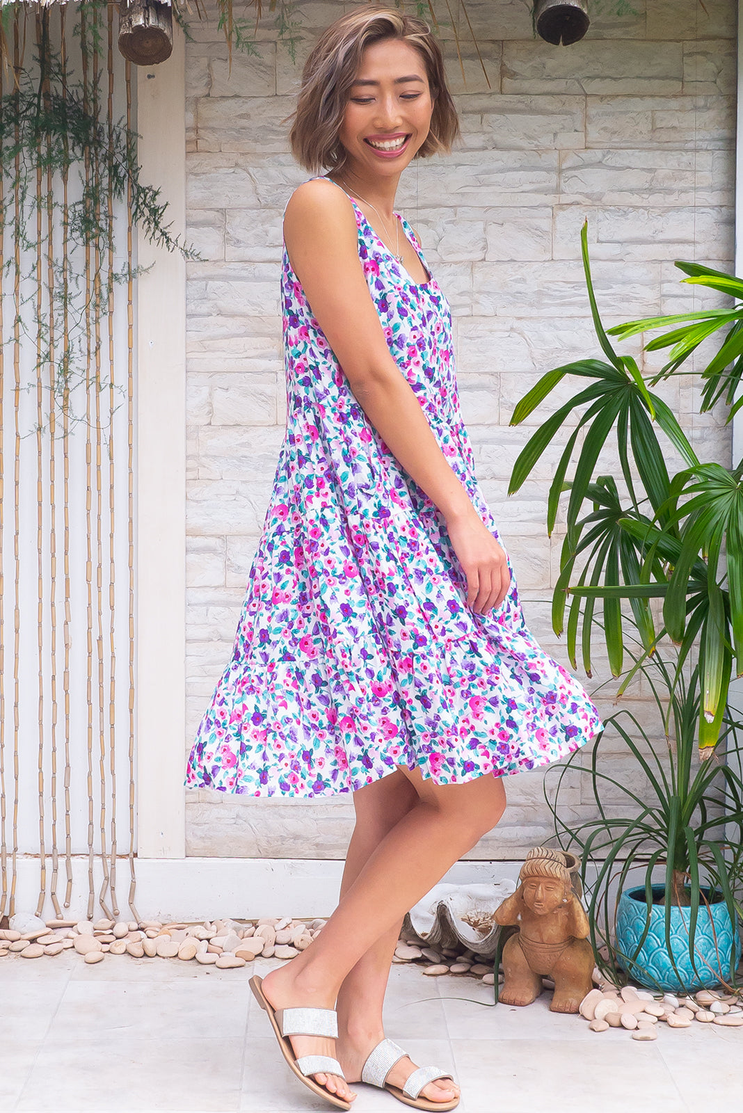 Jina Magenta Dress is a slip on, loose-fit short dress featuring scooped neckline, lined bust, side pockets, tiered, full skirt and 100% rayon in white base with pink and purple floral print.