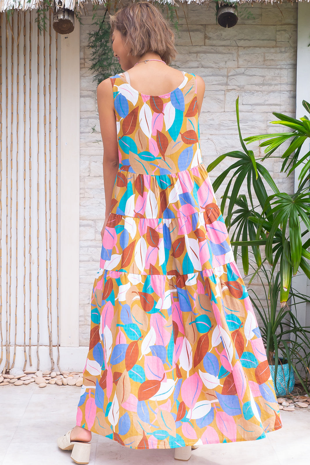 The Jina Magic Leaf Maxi Dress is a loose style dress featuring scooped neckline, lined bust, side pockets, tiered, full skirt and 70% cotton, 30% rayon in caramel base with white, pink, blue, teal and chocolate leaf print.