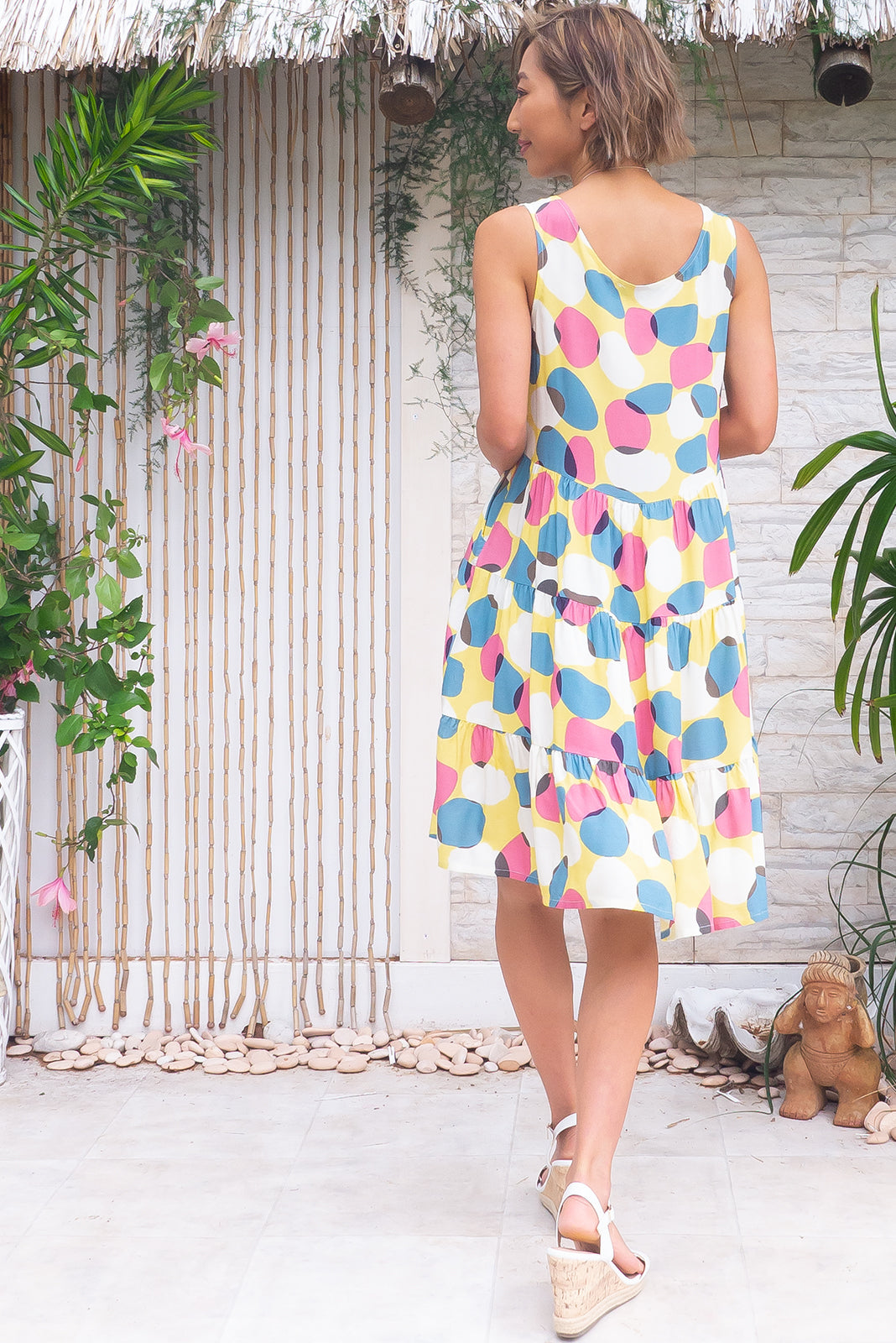 The Jina Zinzi Yellow Dress is a slip on, loose style dress featuring scooped neckline, lined bust, side pockets, tiered, full skirt and 100% rayon in pale yellow base with white, mauve and smoky blue spots print.