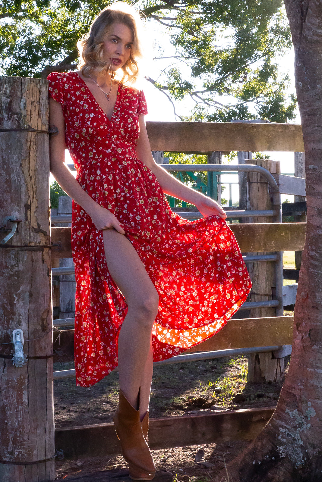 Jude Tangelo Red Midi Dress, bohemian summer style, 100% viscose, elasticated shirred back waist, softly fitted basque waist, functional buttons, deep side pockets, bright red base with small white, gold and black floral print.