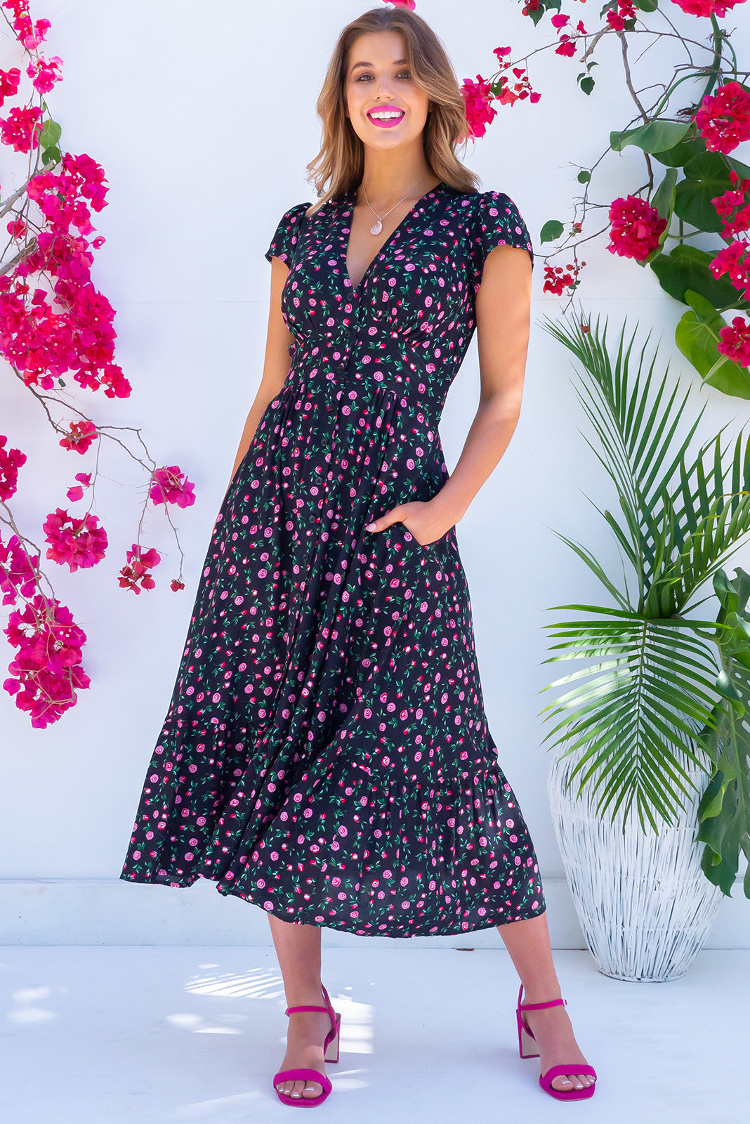 Jude Coco Noir Dress button front vintage inspired date night dress. Black base with rose print on 100% rayon fabric. Features side pockets and cap sleeves.