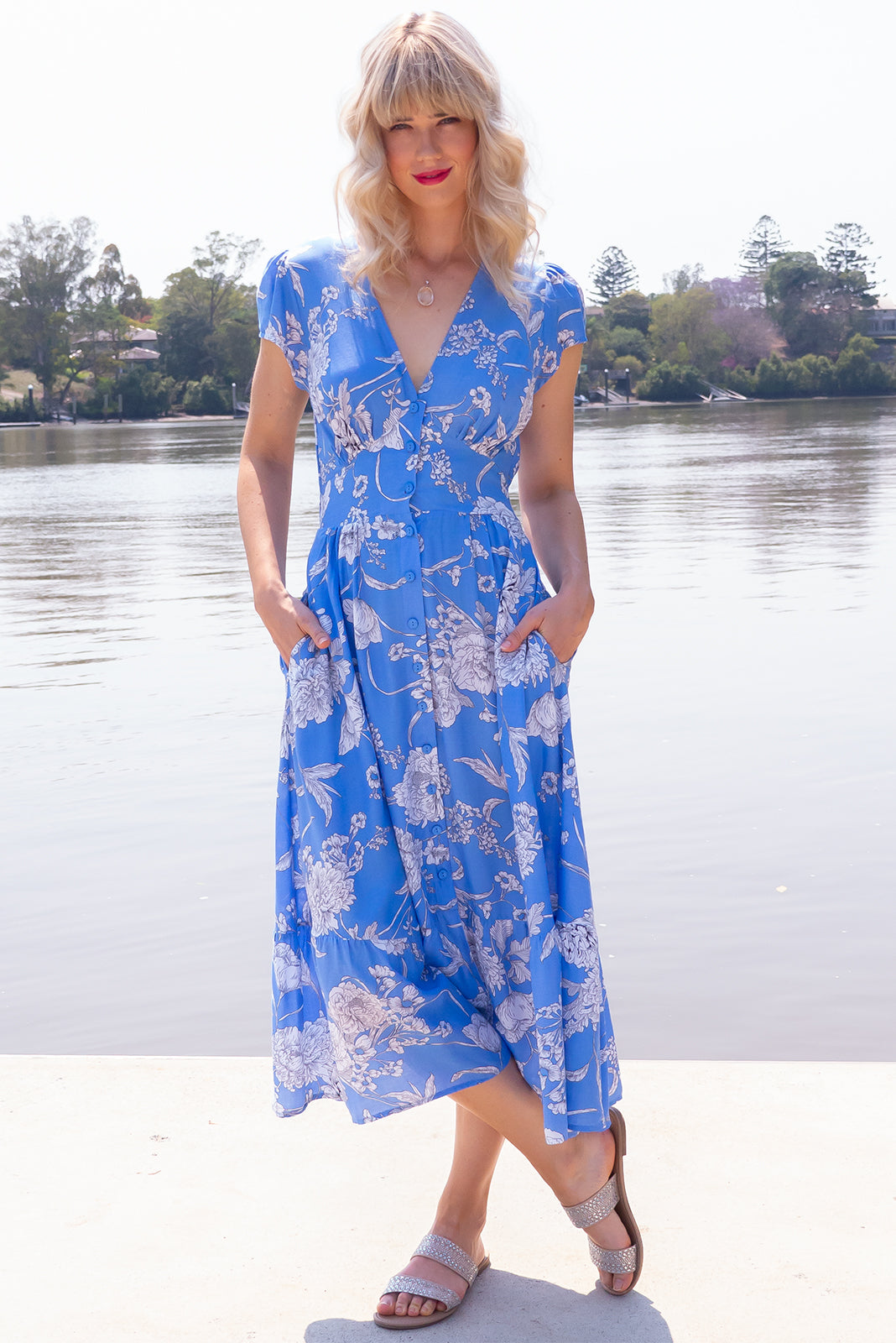 Jude Lisbon Blue Midi Dress, bohemian summer style, 100% viscose, functional button front, softly fitted basque waist, shirred back, cap sleeves, v neck design, deep side pockets, maya blue fabric with large white floral print.