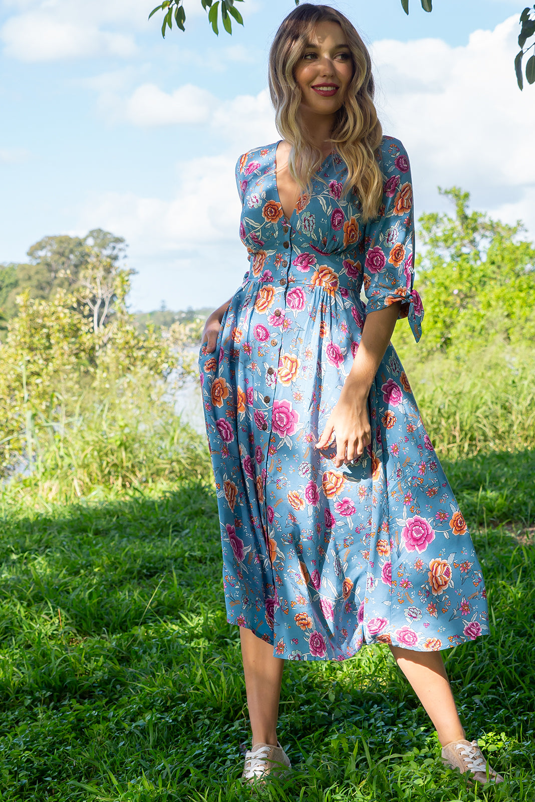 Judith Arctic Roses Midi dress features a vintage inspired fitted basque waist, elasticated waist with a midi sleeve, deep v neck  and fully functional button front in a soft woven rayon fabric with a bohemian romantic bright bohemian floral print on a steel grey base
