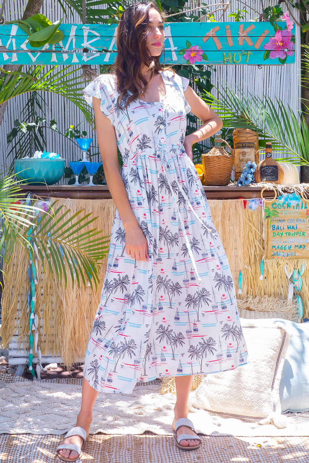 The Juniper Harbour White Maxi Dress features functional button down detailing to waistline, side pockets, adjustable drawstring waist and 100% viscose in white base with retro sail boat and palm print.