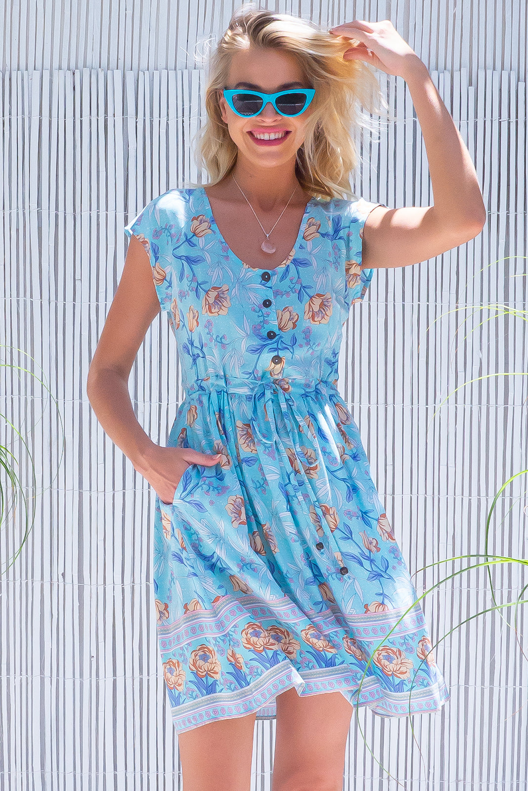 The Juniper Cornflower Blue Dress features functional button down chest to waistline, cap sleeves, side pockets, adjustable drawstring waist and 100% viscose in light blue base with a large floral print.
