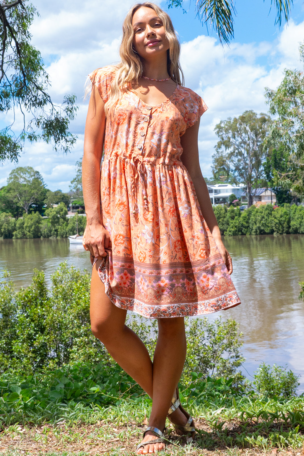 The Juniper Daybreak Orange Dress features functional button down chest to waistline, cap sleeves, side pockets, adjustable drawstring waist and woven 100% viscose in light orange base with a bohemian floral print and border feature.
