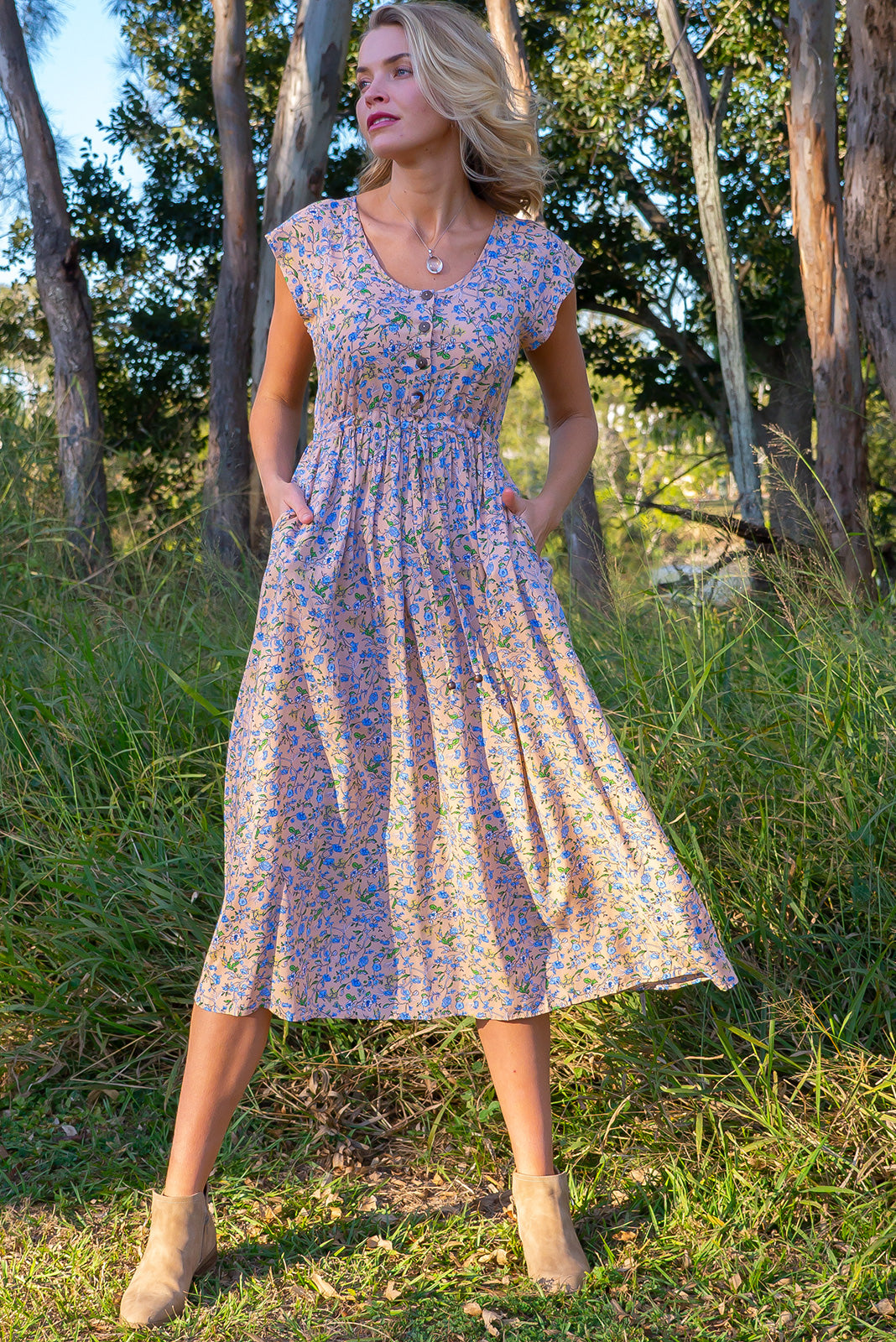 Juniper Ecru Haze Maxi Dress is much welcomed and adored featuring functional button down detailing to waistline, side pockets, adjustable drawstring waist in warm Ecru base with a blue floral vine print.