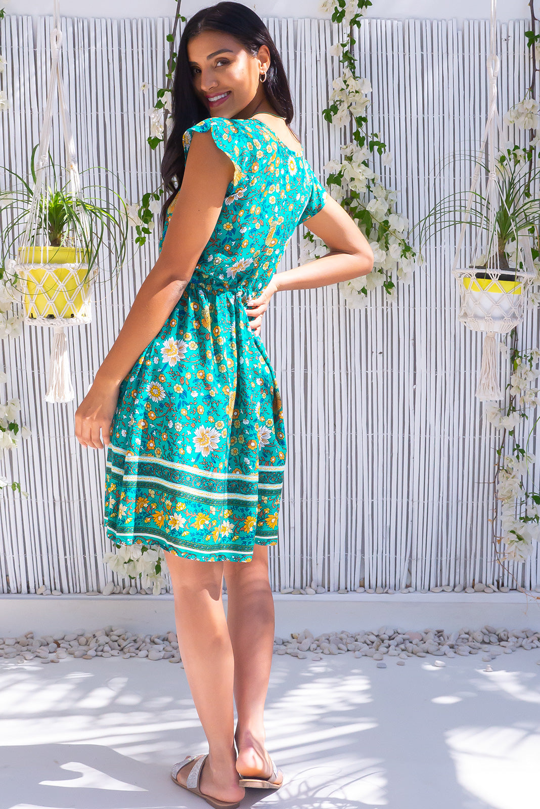 Juniper Green Acres Dress features functional button down chest to waistline, side pockets, adjustable drawstring waist and woven 100% rayon in bold green base with folk floral print, and border feature.