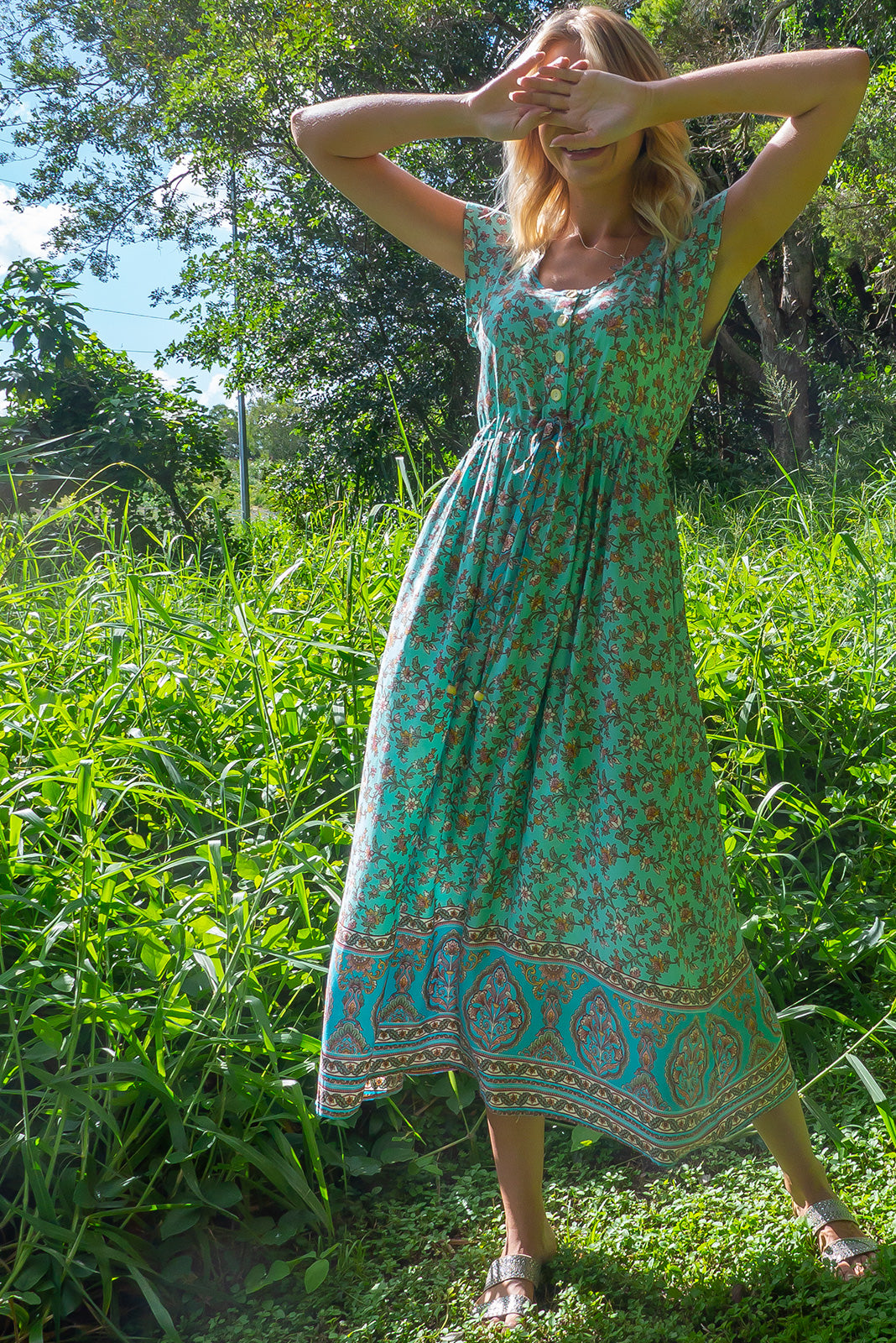 The Juniper Mint Sandrine Maxi Dress featuring functional button down detailing to waistline, side pockets, adjustable drawstring waist, neck binding and drawstring may feature border print and 100% viscose in mint/aqua base with an all-over print with blue border feature.