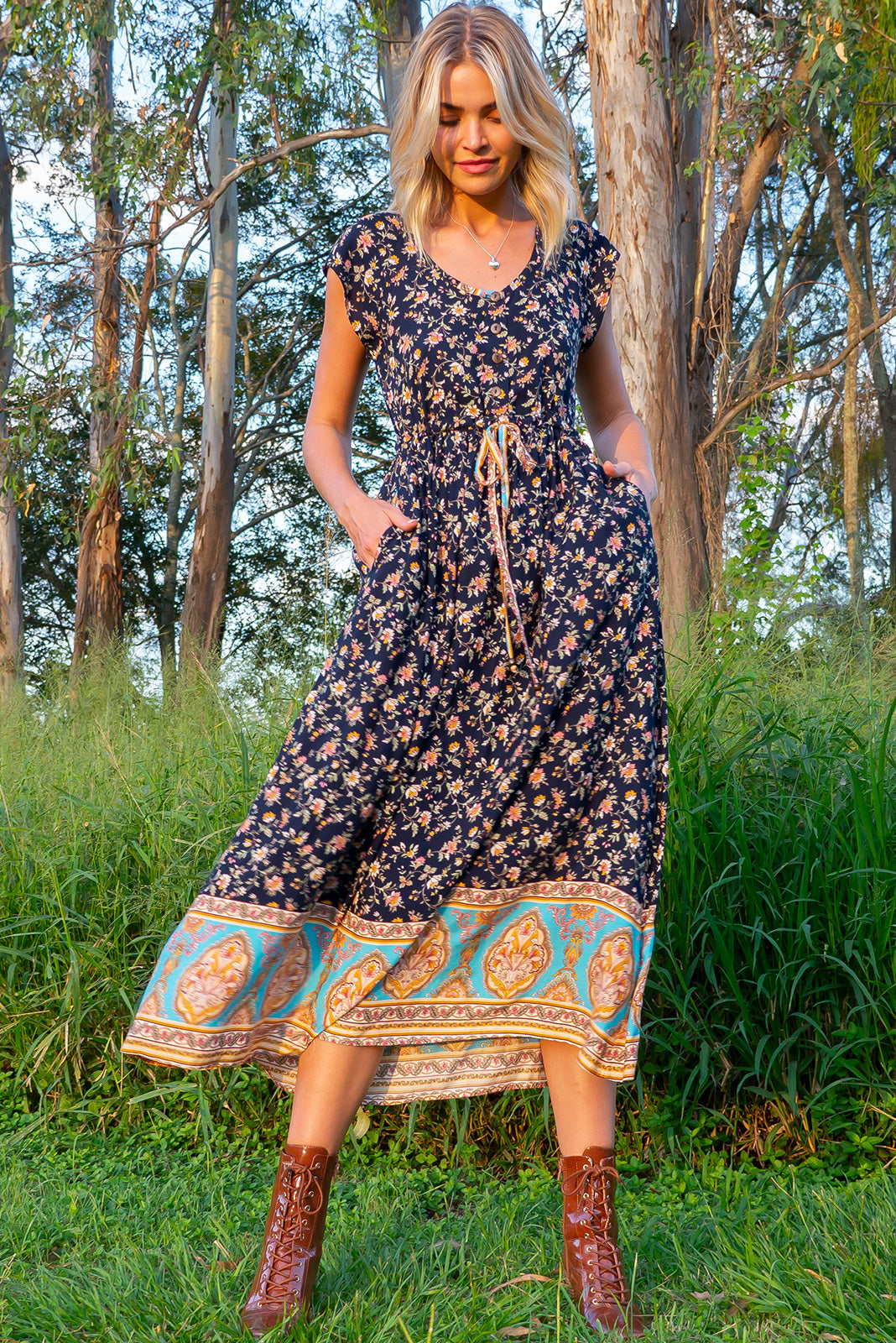 The Juniper Navy Novello Sandrine Maxi Dress features functional button down detailing to waistline, side pockets, adjustable drawstring waist and 100% viscose in ink base with vintage floral print with blue border feature.