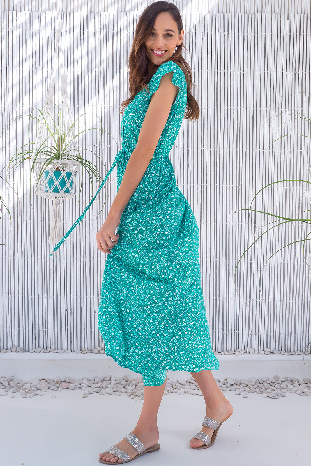 The Juniper Orla Green Maxi Dress featuring functional button down detailing to waistline, side pockets, adjustable drawstring waist and 100% rayon in green base with white floral motif.