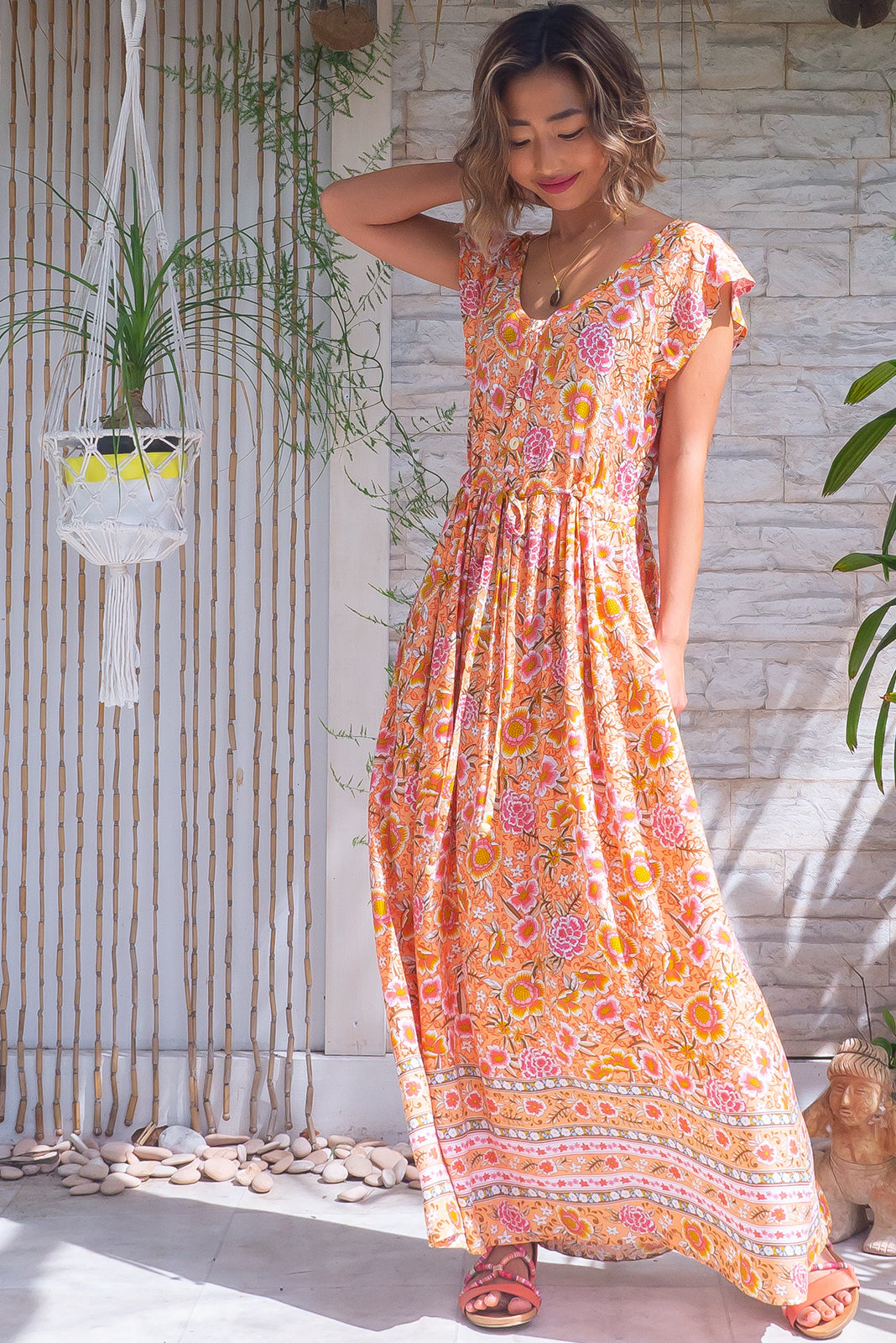 The Juniper Peach Sandrine Maxi Dress features functional button down detailing to waistline, side pockets, adjustable drawstring waist, border feature and 100% viscose in pale orange base with vintage floral print.
