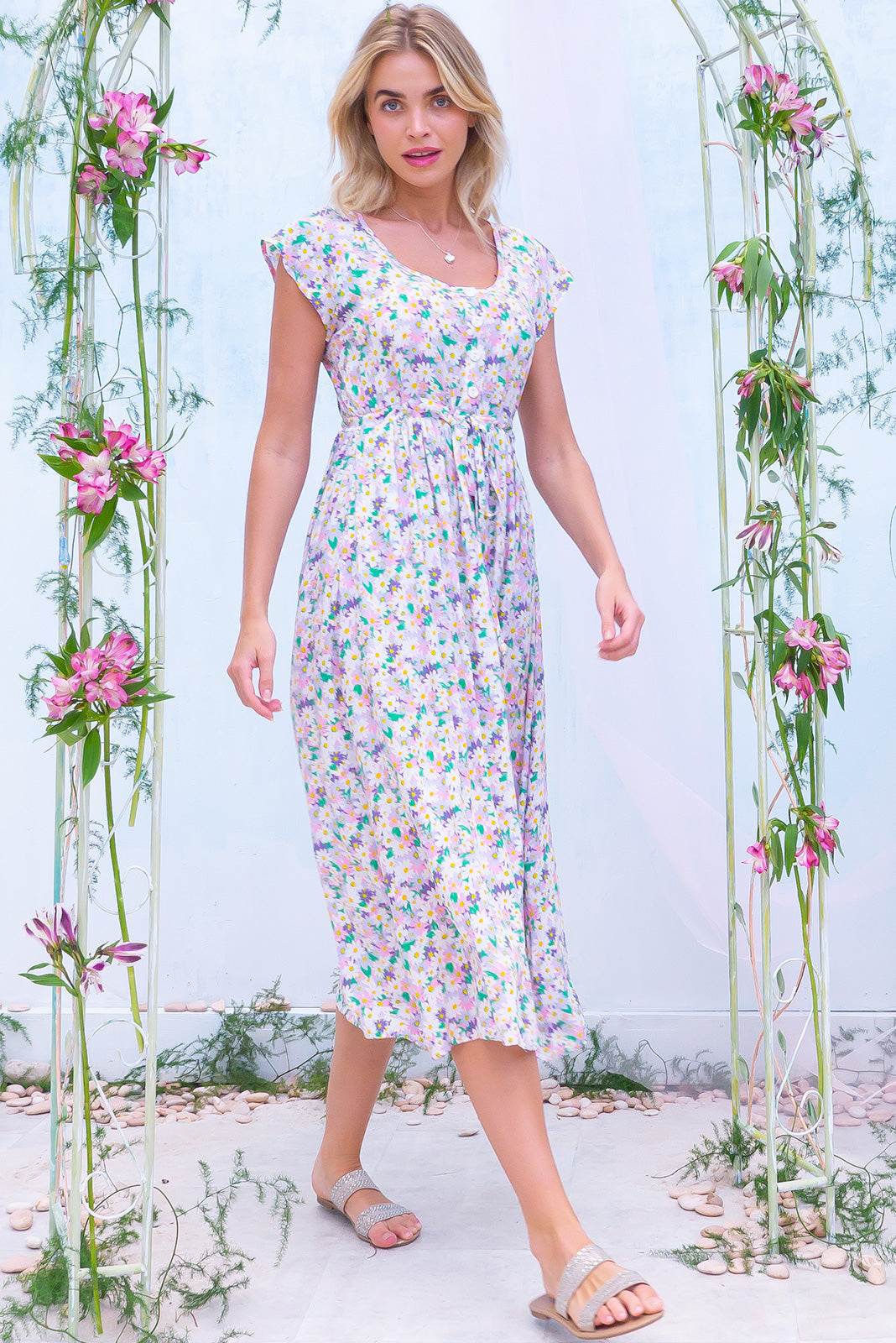 The Juniper Pink Spritz Maxi Dress features functional button down detailing to waistline, side pockets, adjustable drawstring waist and 100% viscose in pastel all-over floral print.