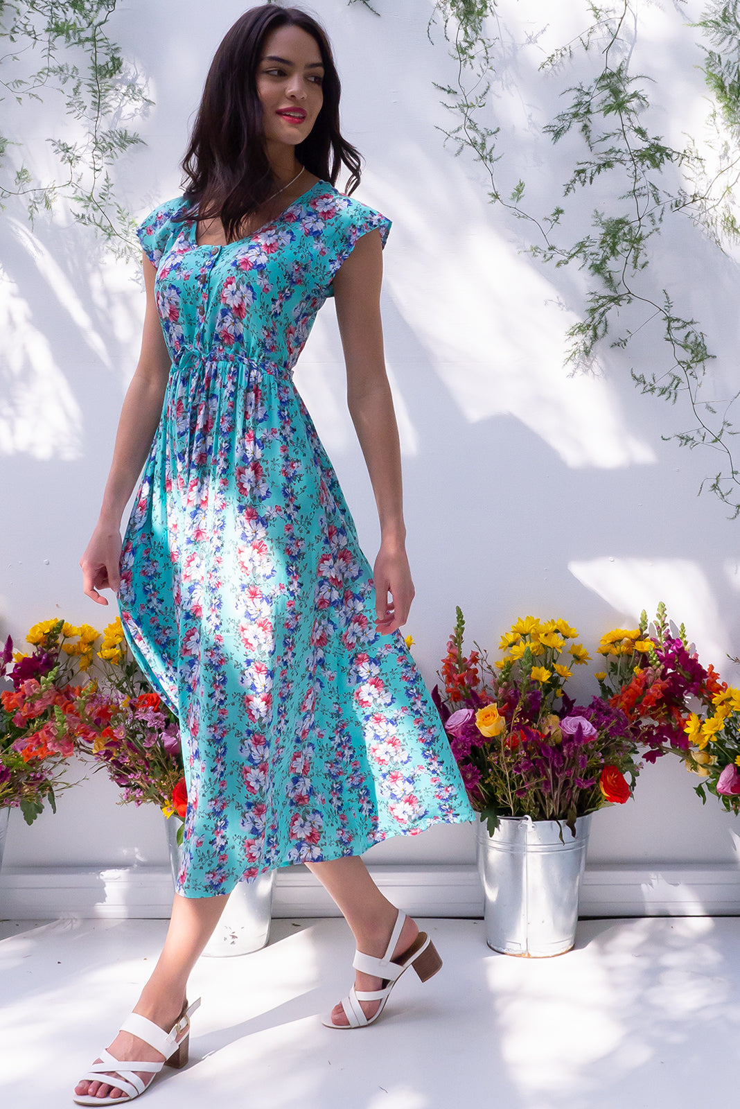 The Juniper Sky Trellis Maxi Dress features functional button down detailing to waistline, cap sleeves, side pockets, adjustable drawstring waist and 100% rayon in turquoise base with vintage floral vine print in white, pink and blue.