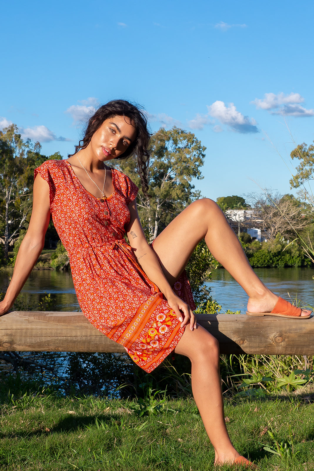 Juniper Valencia Orange Dress features functional button down chest to waistline, wide pockets, adjustable drawstring waist and 100% viscose in orange/amber boho folk floral pattern and border feature.