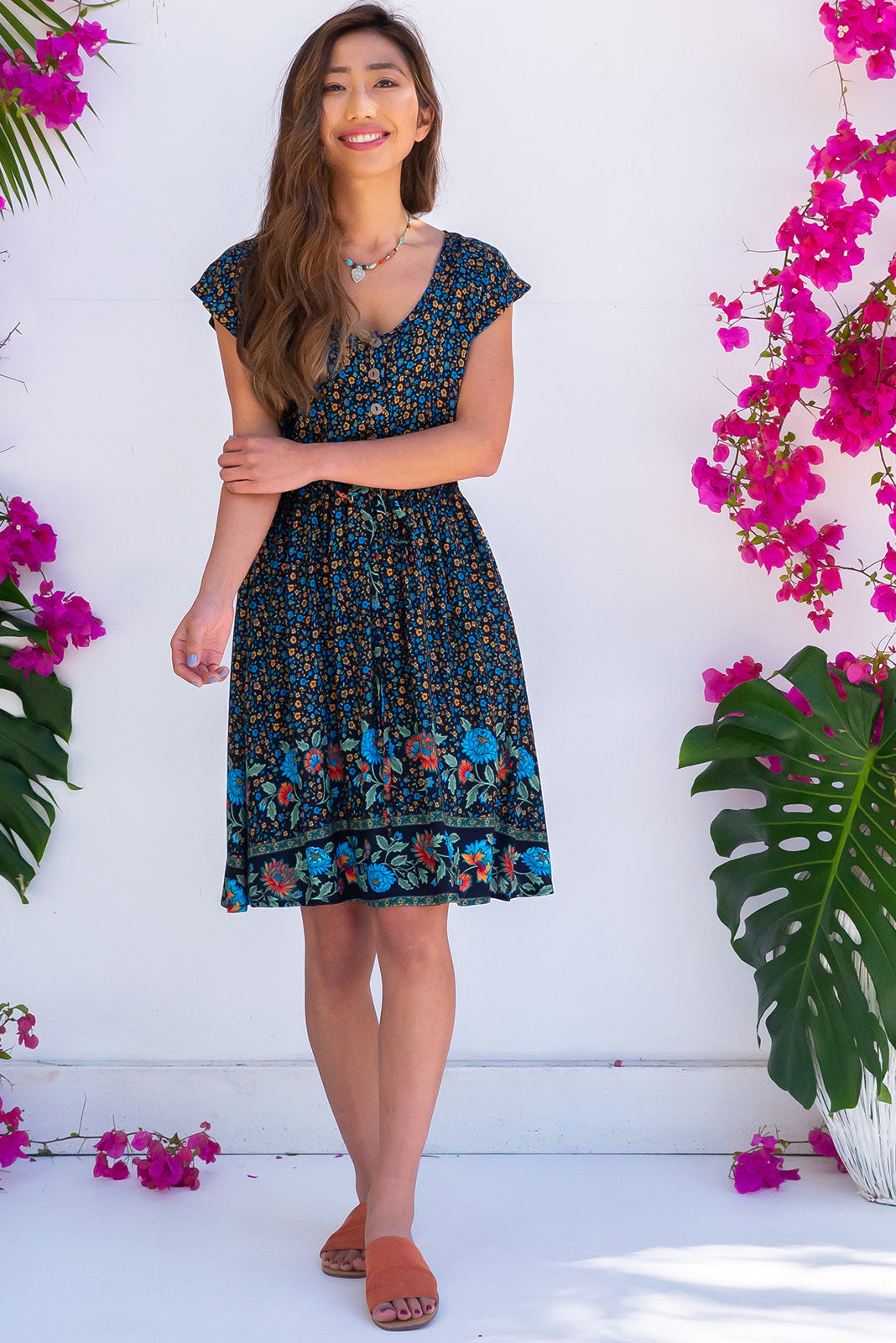 Juniper Folklore Navy Dress is a bohemian inspired summer dress. A bright floral print on a black based rayon fabric. Features side pockets and a drawstring waist.