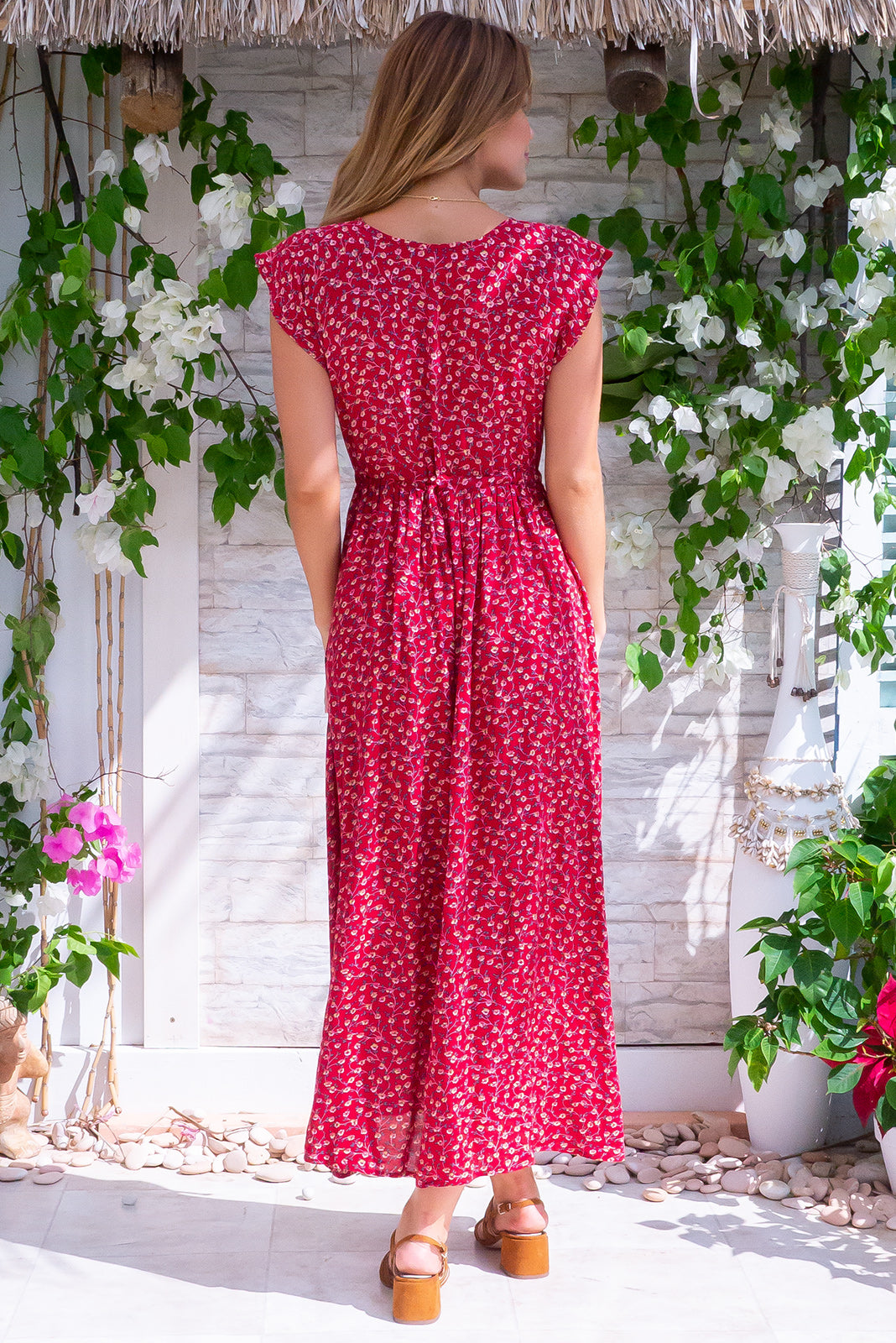 Juniper Red Earth Maxi Dress in nature-inspired floral 100% viscose fabric. Including side pockets, adjustable drawstring waist, cap sleeve, functional top buttons in deep red base with pink, white and forest green floral print.