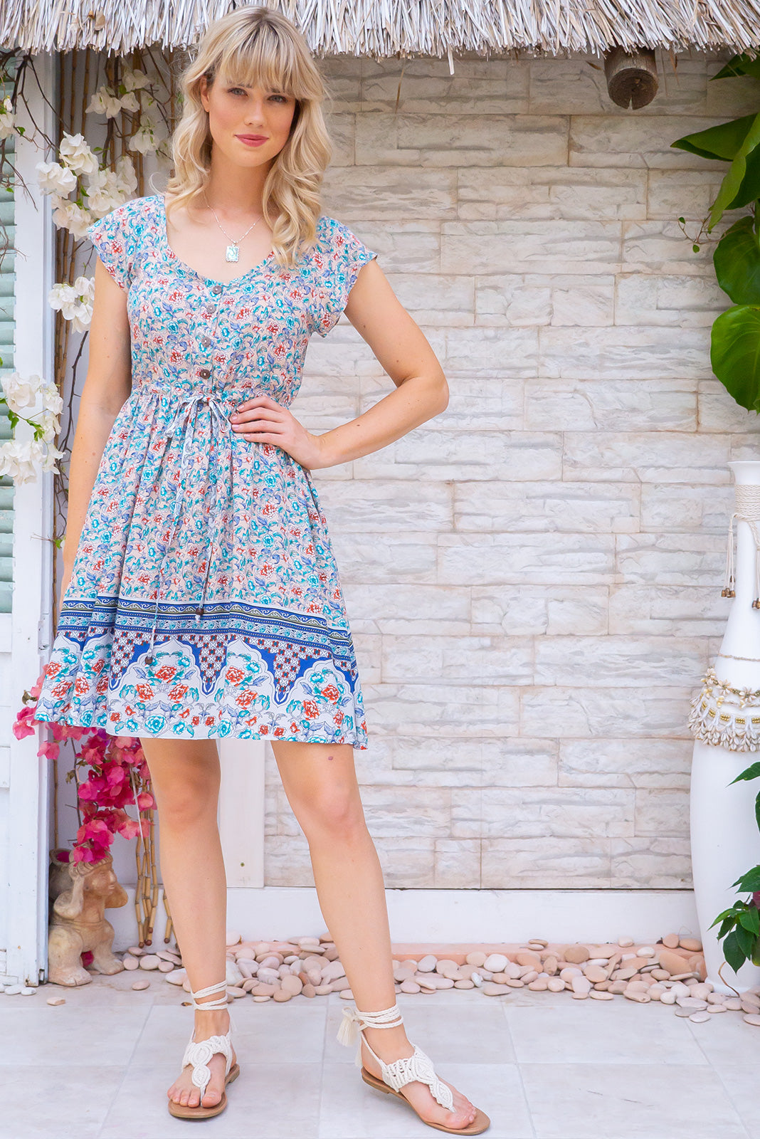 Juniper Sonnet Cream Dress, bohemian summer style, 100% rayon, functional button down to waistline, cap sleeves, side pockets, adjustable drawstring waist, cream base with small orange, teal and blue wildflower print, complimentary border print.