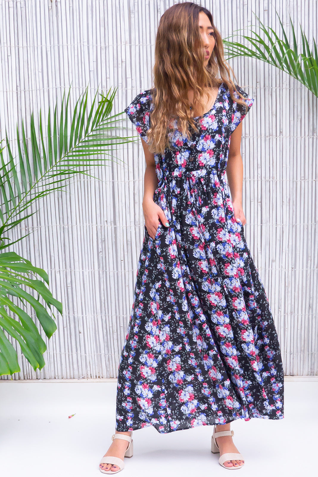 Juniper Trellis Noir Maxi Dress is a fabulous day maxi frock featuring functional button down detailing to waistline, cap sleeves, side pockets, adjustable drawstring waist, black base with blue, steel blue, mauve and sage green floral print in woven 100% rayon.