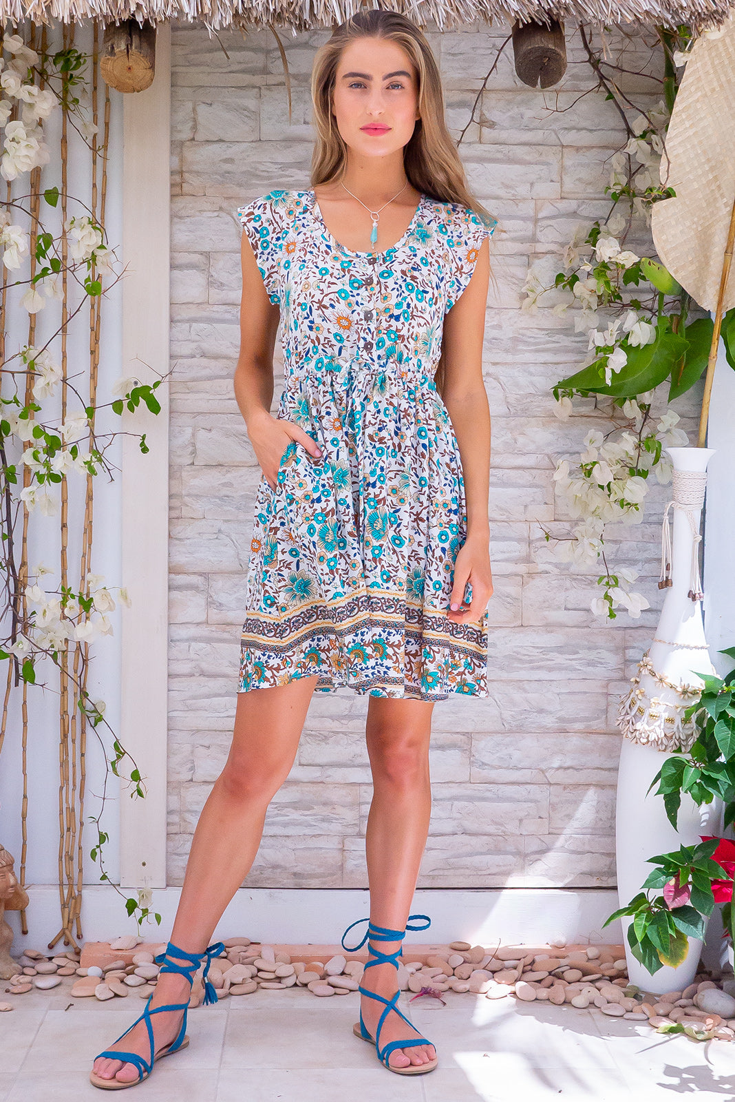 Juniper Spring Song White Mini Dress is a light-weight day dress featuring woven 100% viscose, functional button down chest to waistline, side pockets, adjustable drawstring waist in white base with multi-tonal floral design.