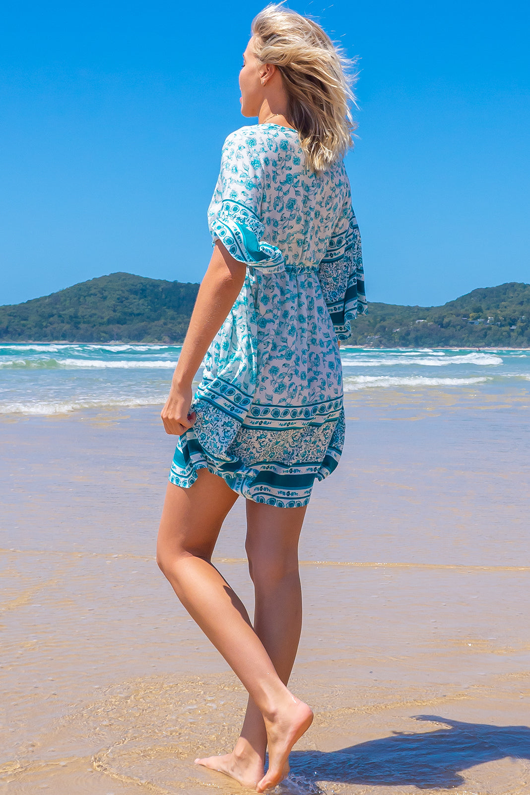 Perfect beach style, the Layla Bahama Sea Mini Dress features deep V, caftan sleeves, adjustable embroidered multicoloured drawstring waist and 100% rayon in white base with turquoise print and border feature.