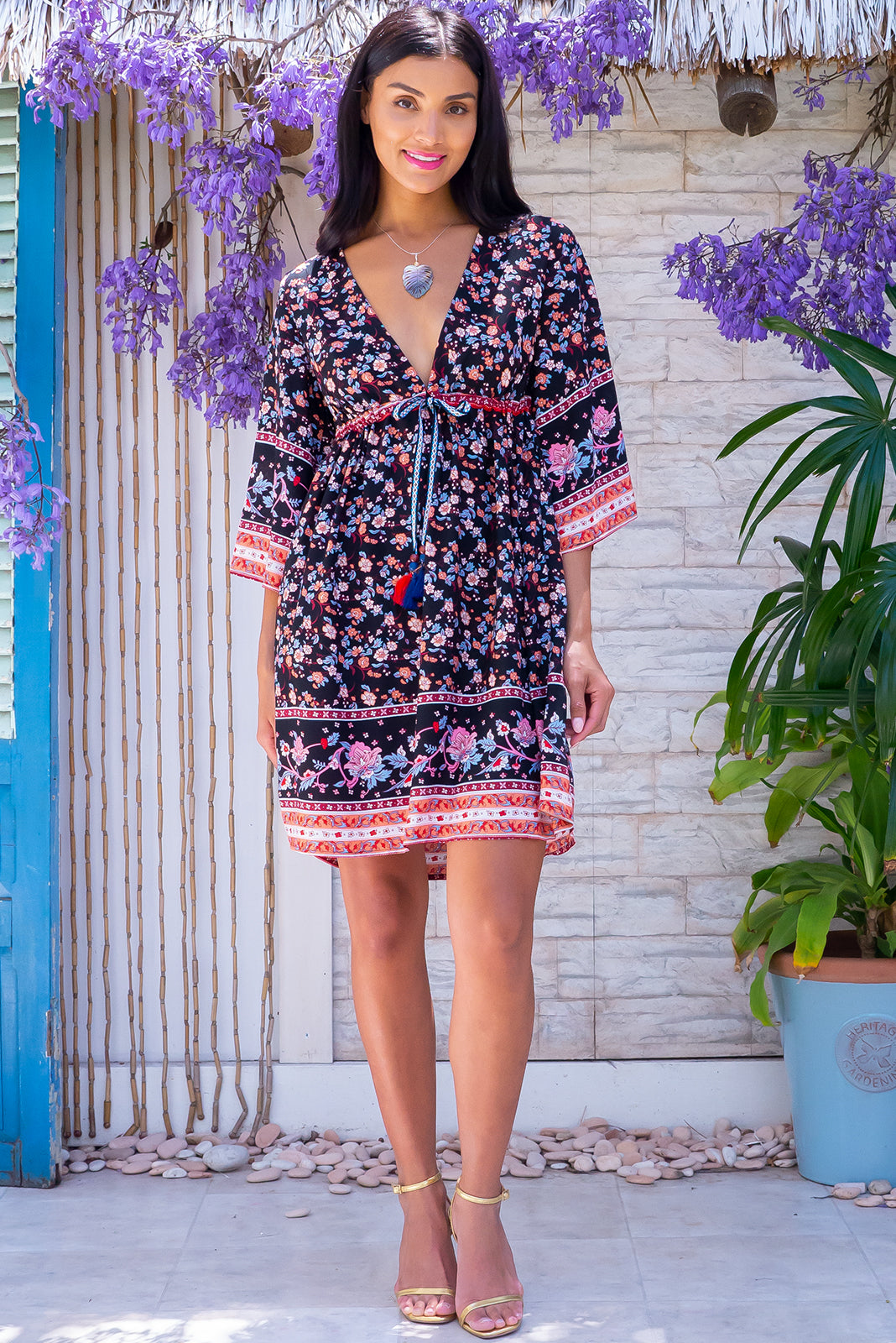 The Layla Island Night Mini Dress features caftan sleeves, adjustable drawstring waist, side pockets and 100% rayon in black base with colourful vine print and border feature.