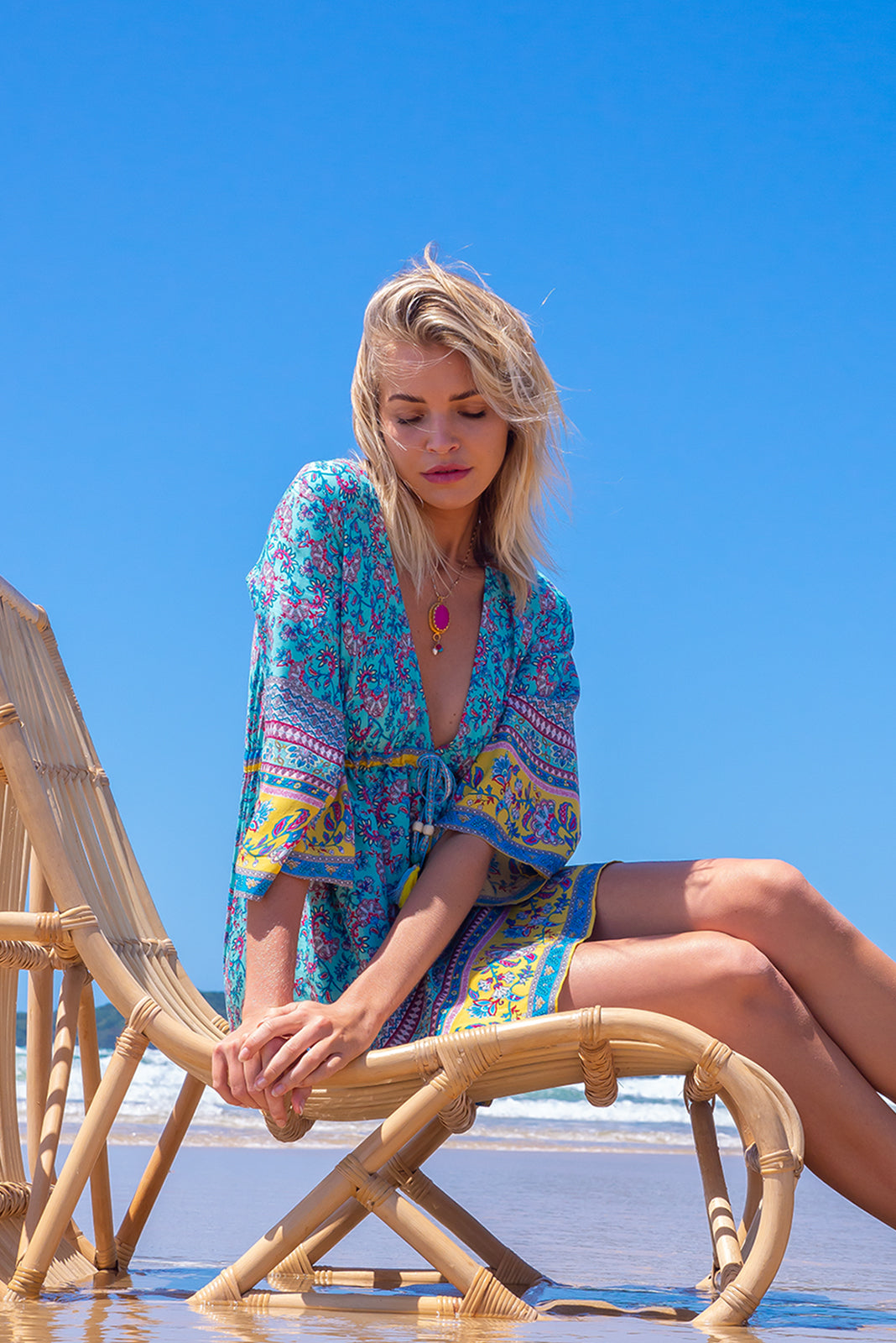 The Layla Sea and Sun Mini Dress features deep V plunge neckline, caftan sleeves, adjustable drawstring waist, embroidered multicoloured drawstring with tassels and beads, side pockets and 100% rayon in blue base with fun print and yellow border feature.