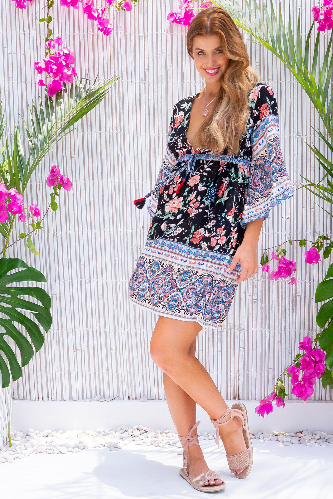 Layla Wood Rose Black Mini Dress, bohemian summer style, 100% rayon, adjustable drawstring waist, multicoloured braided drawstring with bead detail, side pockets, black base with medium multicoloured floral print featuring coral, peach, light blue and mint and complimentary border pattern.