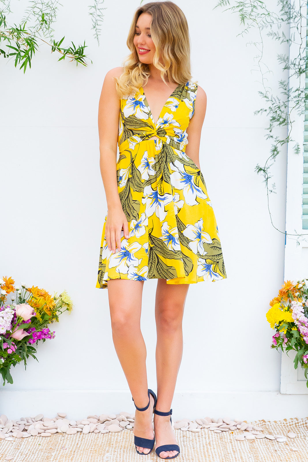 Little Darling Yellow Trumpet Wrap Dress tie front wrap dress with an elastic waist and a plunging v neckline made from a 100% rayon fabric in a yellow floral print