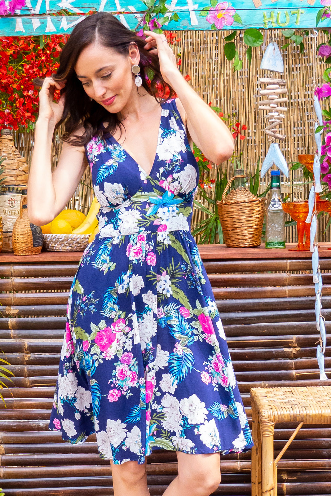 Little Lola Del Mar dress features a vintage inspired fitted basque waist and elasticated waist with a sleeveless design and deep v neck the fabric is a soft woven rayon in bright navy tropical floral print