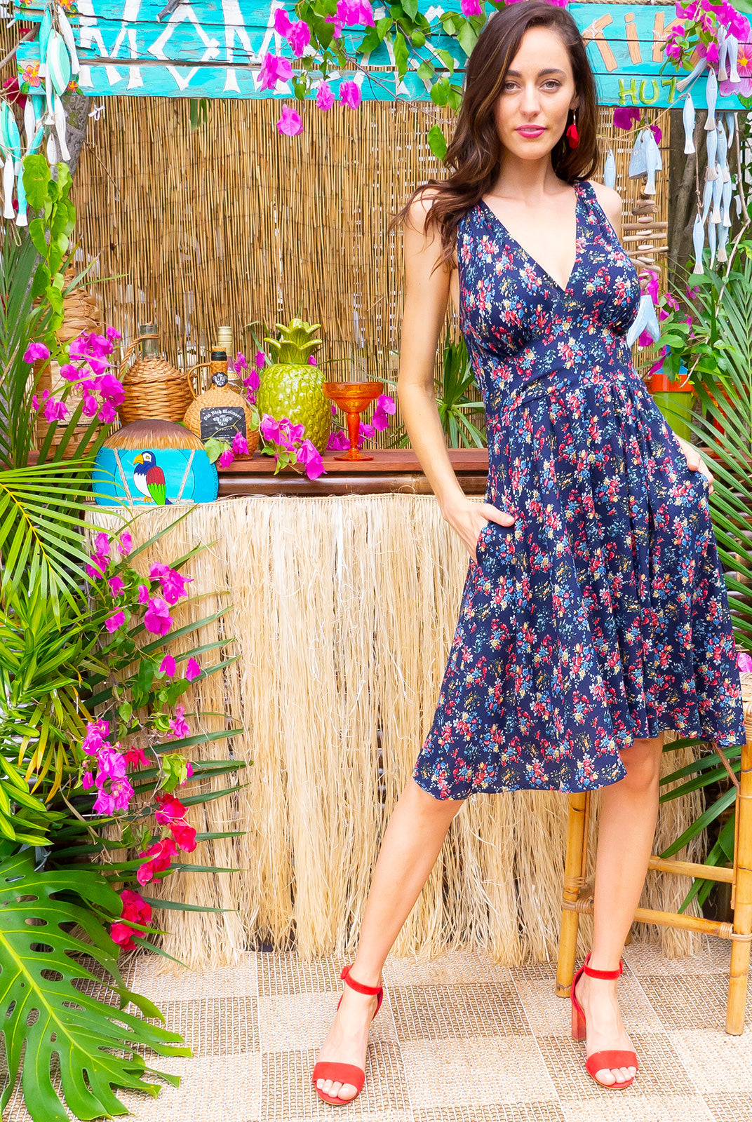 Little Lola Ditzy Navy dress features a vintage inspired fitted basque waist and elasticated waist with a sleeveless design and deep v neck the fabric is a soft woven rayon in a dark navy ditzy bouquet floral print