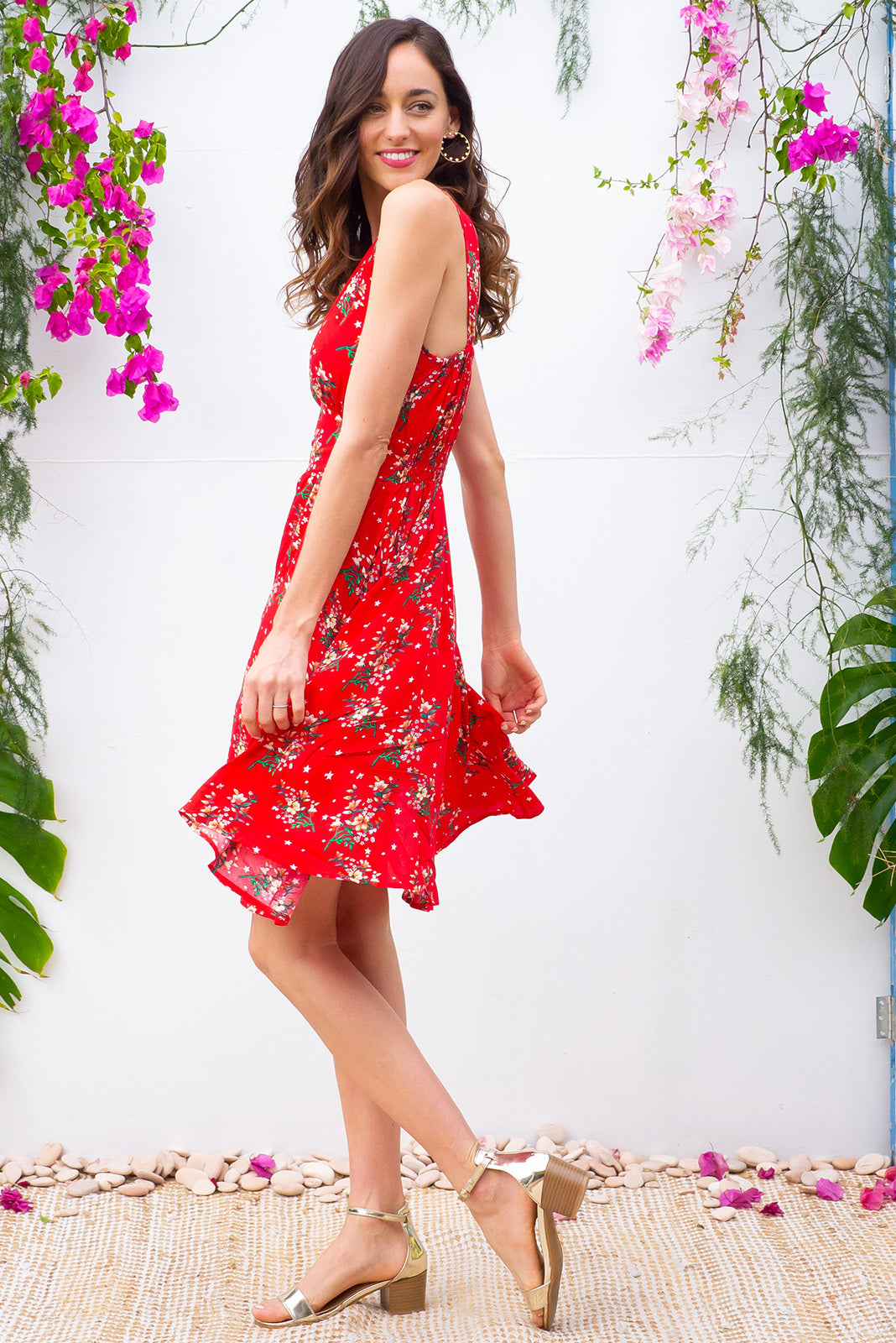 Little Lola Red Stars dress features a vintage inspired fitted basque waist and elasticated waist with a sleeveless design and deep v neck the fabric is a soft woven rayon in a bright red stars and floral print