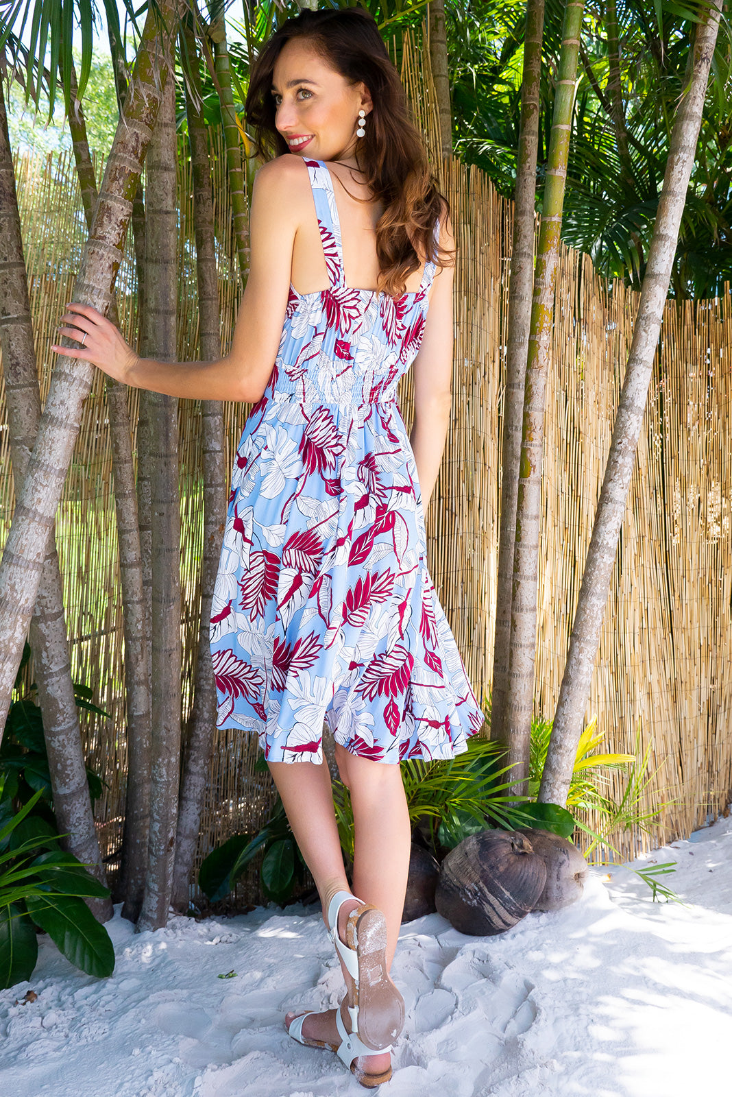 Little Lola Jungle Sky dress features a vintage inspired fitted basque waist and elasticated waist with a sleeveless design and deep v neck the fabric is a soft woven rayon in sky blue and dark red tropical leaf print