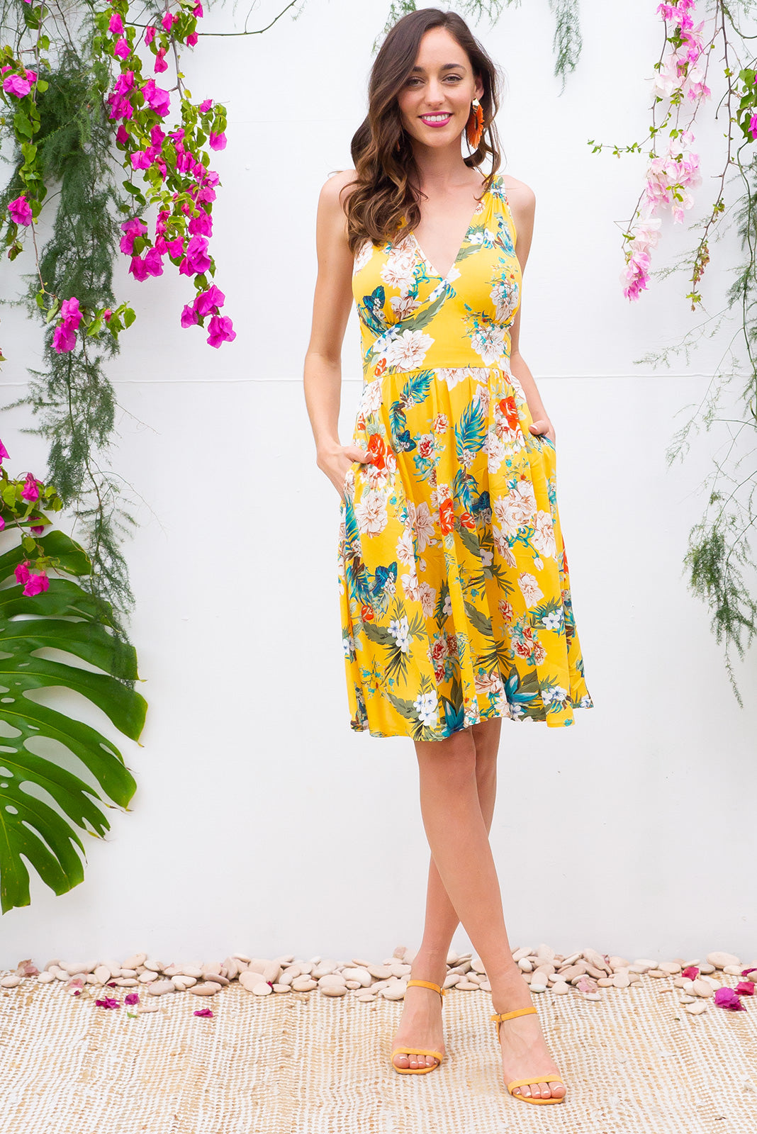 Little Lola Sunshine Yellow dress features a vintage inspired fitted basque waist and elasticated waist with a sleeveless design and deep v neck the fabric is a soft woven rayon in a yellow based tropical floral print