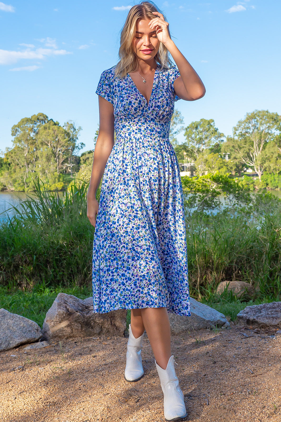 The Lizzie Delta white Dress features fitted basque waist with gathered bust, waist features elastic shirring at back, petite side pockets and 100% rayon in white base with gorgeous blue floral print.