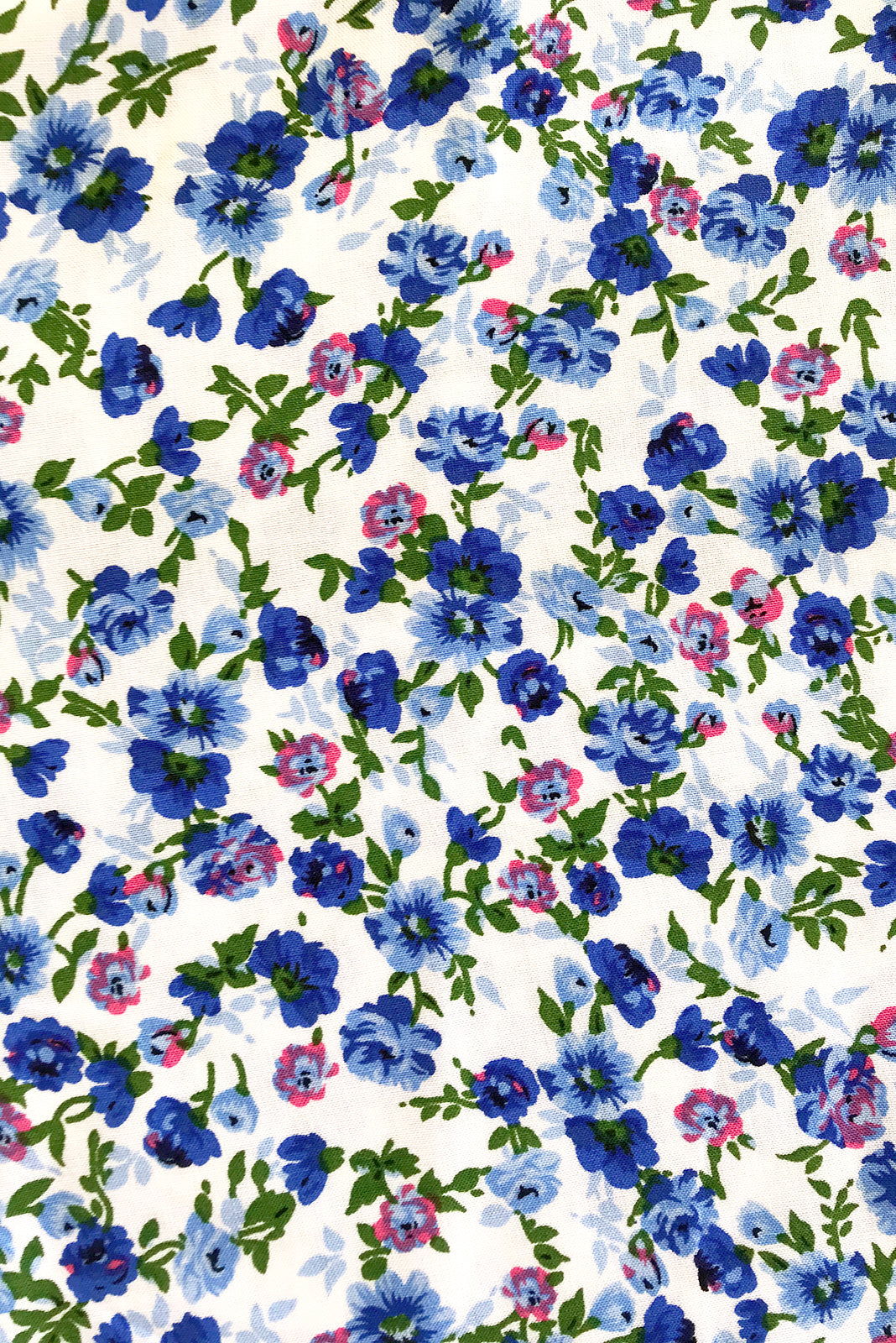 Fabric swatch of Lizzie Delta white Dress featuring 100% rayon in white base with gorgeous blue floral print.