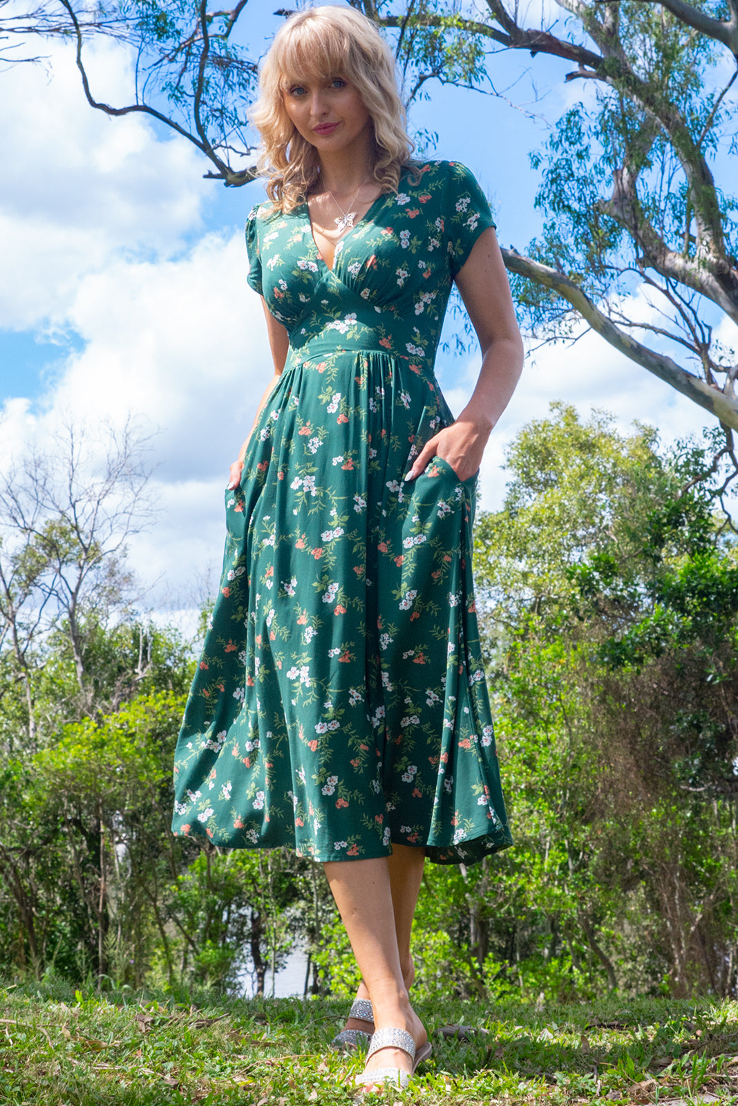 The Lizzie Green Gables Dress featuring fitted basque waist with gathered bust, waist features elastic shirring at back, petite side pockets and 100% rayon in muted green base with vintage inspired floral print.