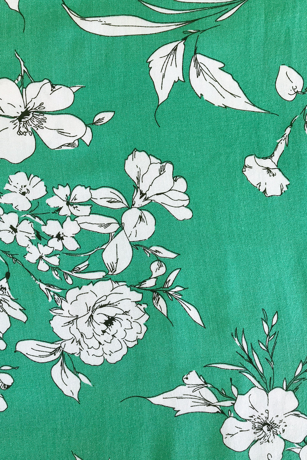 Fabric Swatch of Lizzie Mono Meadow Dress featuring 100% rayon in soft, shamrock green base with white floral print.