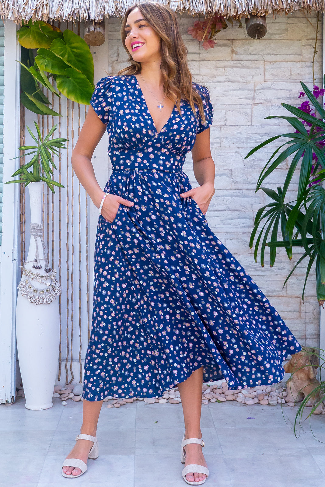 The Lizzie Navy Flirt Dress features fitted basque waist with gathered bust, waist features elastic shirring at back, deep side pockets and 100% rayon in navy base with daisy print.