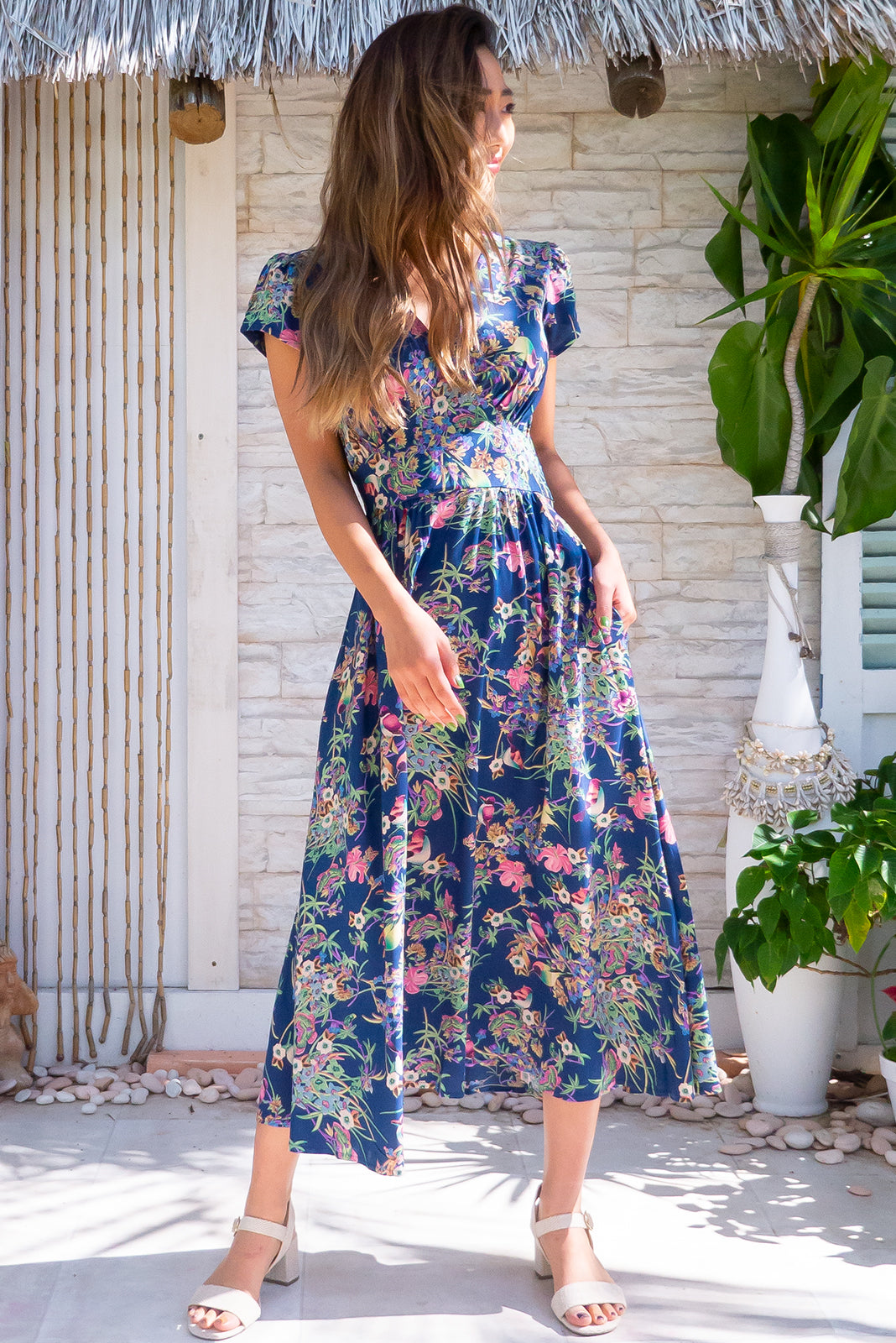 Lizzie Navy Honeyeater features fitted basque waist with gathered bust, elastic shirring at back of waist, deep side pockets, navy blue base with vintage floral print in pinks, greens, creams and blues, with sunbirds scattered throughout in woven 100% rayon.