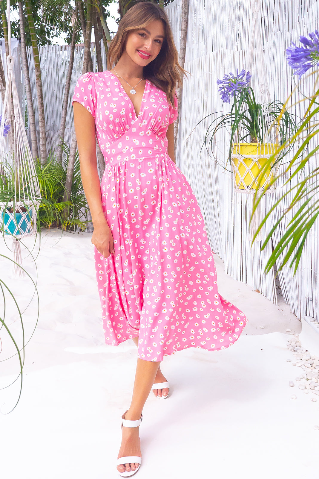 The Lizzie Pink Spring Dress features fitted basque waist with gathered bust, waist features elastic shirring at back, petite side pockets and 100% rayon in bright, taffy pink base with sweet daisy print.