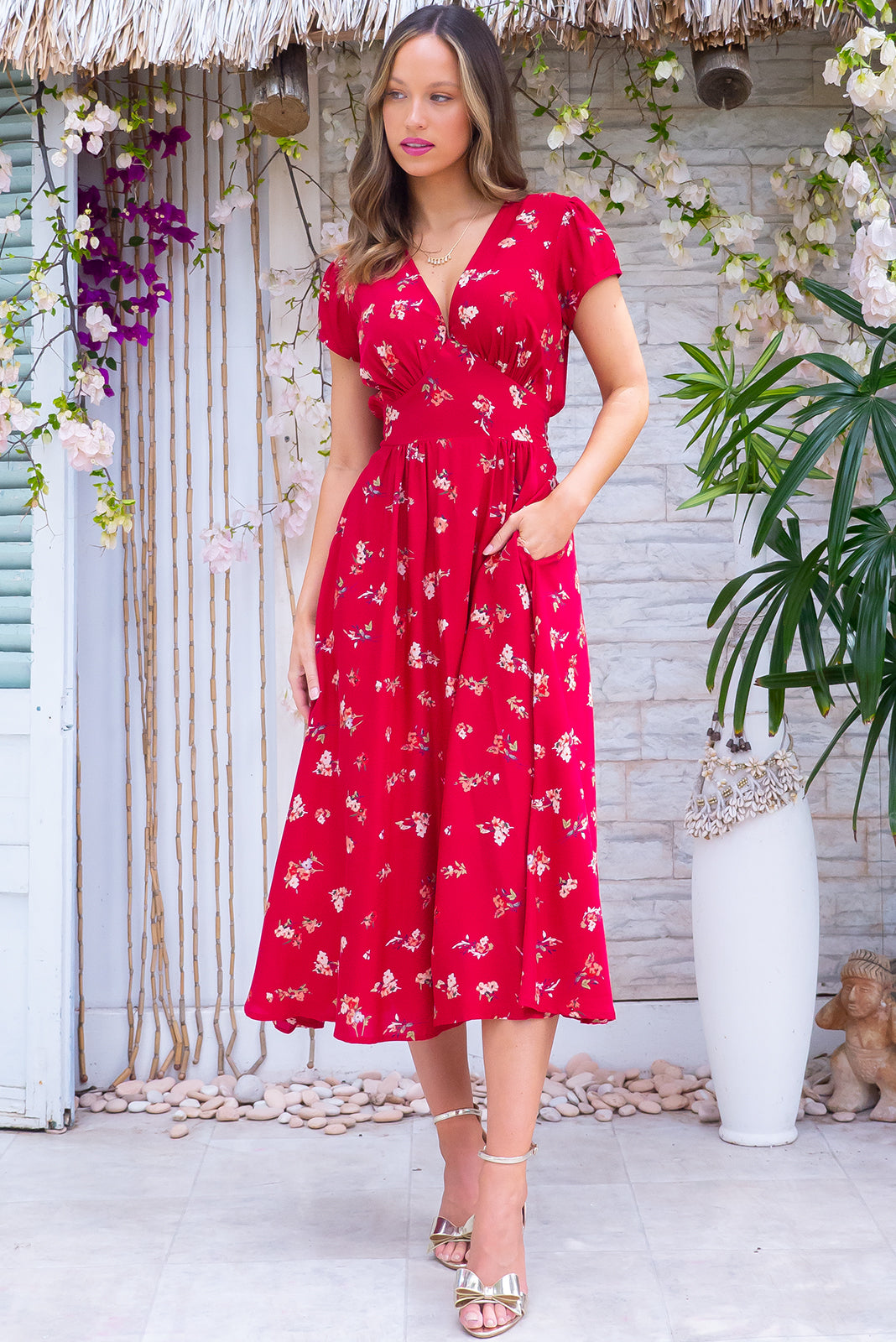 The Lizzie Red Treasure Dress features fitted basque waist with gathered bust, waist features elastic shirring at back, side pockets and 100% rayon in deep red base with scattered floral print.
