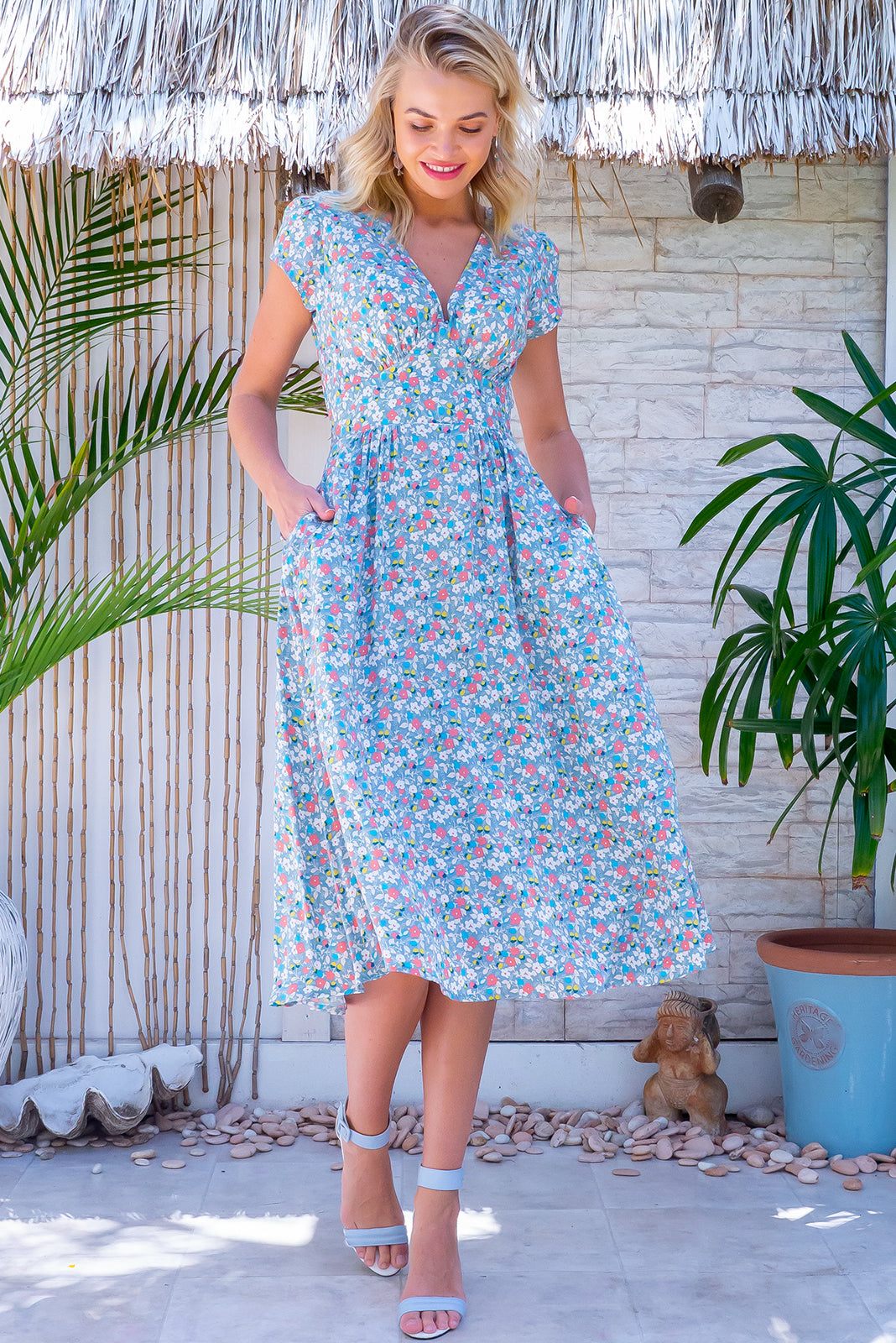 The Lizzie Steel Blue Dress features fitted basque waist with gathered bust, deep side pockets and 100% rayon in steele blue base with spring inspired floral print.