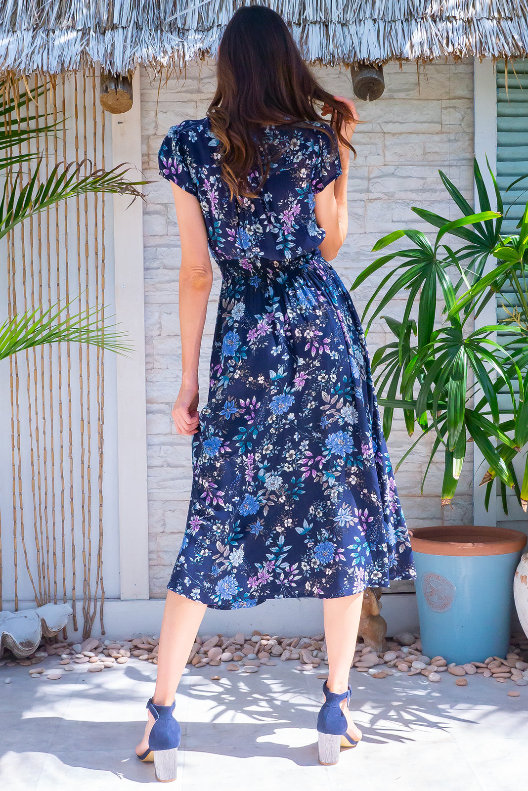 The Lizzie Wildflower Navy Dress features fitted basque waist with gathered bust, waist features elastic shirring at back, deep side pockets and 100% rayon in navy base with lilac, blue and green floral print.