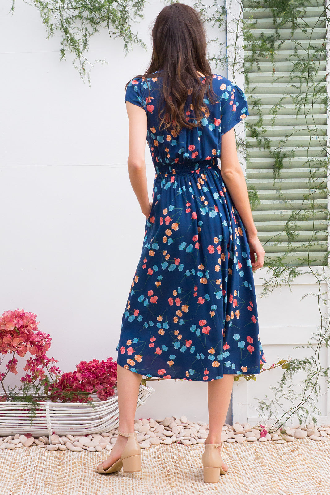 Lizzie Blue Poppies Midi dress features a vintage inspired fitted basque waist and elasticated waist with a cap sleeve and deep v neck the fabric is a soft woven rayon in a soft navy poppy floral print