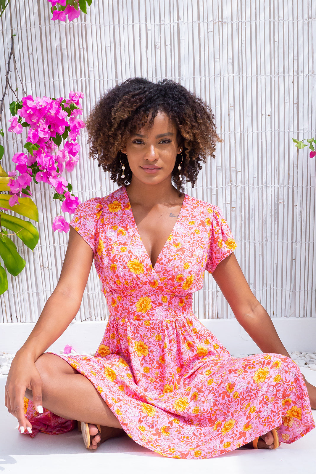 Lizzie Emma Pink Midi Dress inspired by retro frocks from the 1940s and 1950s features fitted basque waist with gathered bust, waist features elastic shirring at back, deep side pockets, bright pink base with orange and peach floral print in woven 100% rayon.