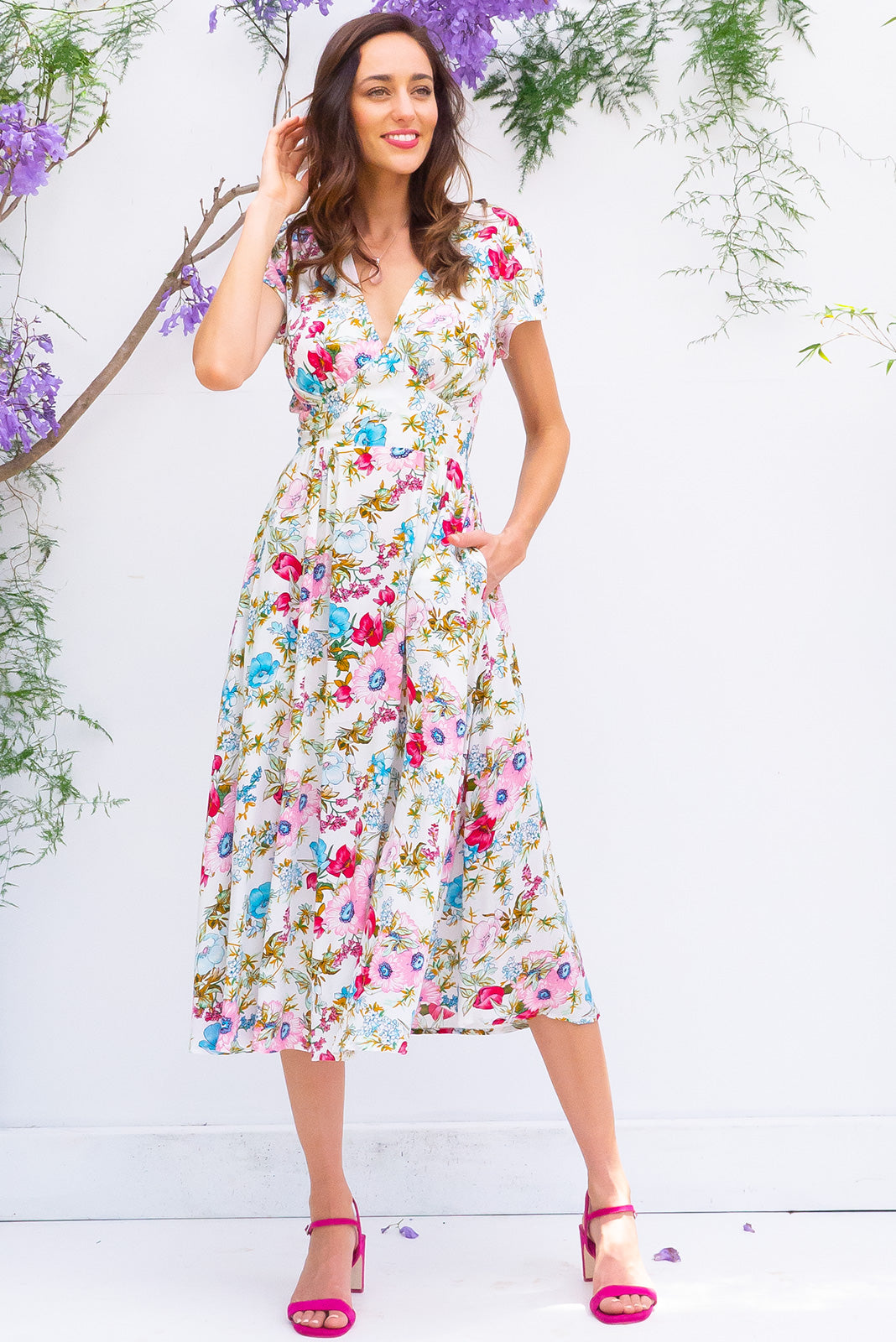 Lizzie Jolie Posy Midi dress features a vintage inspired fitted basque waist and elasticated waist with a cap sleeve and deep v neck the fabric is a soft woven rayon in a crisp white and brightly coloured bouquet floral print