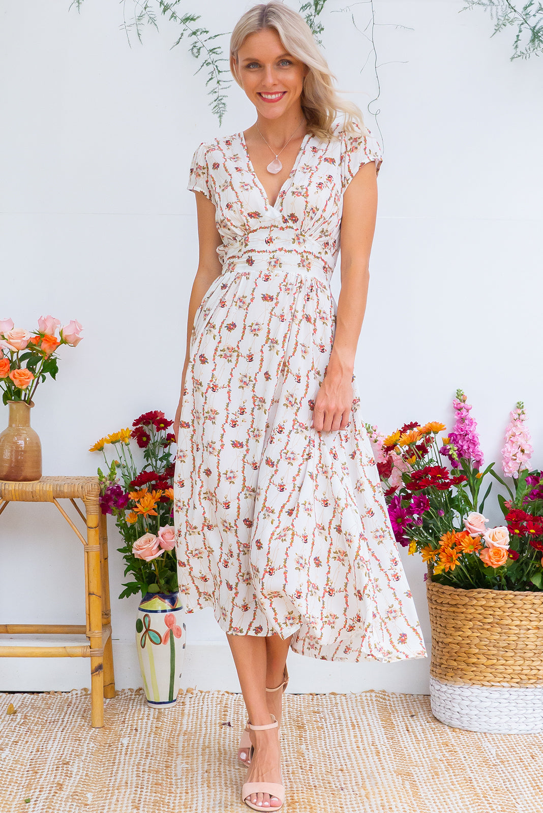 Lizzie Garlands Midi dress features a vintage inspired fitted basque waist and elasticated waist with a cap sleeve and deep v neck the fabric is a soft woven rayon in a soft white floral garland print