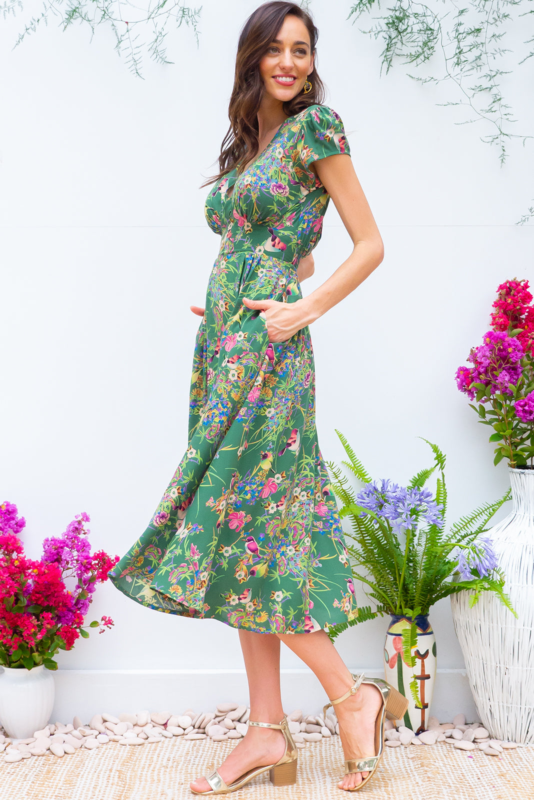 Lizzie Green Honey Eater Midi dress features a vintage inspired fitted basque waist and elasticated waist with a cap sleeve and deep v neck the fabric is a soft woven rayon in a forest green floral and bird print