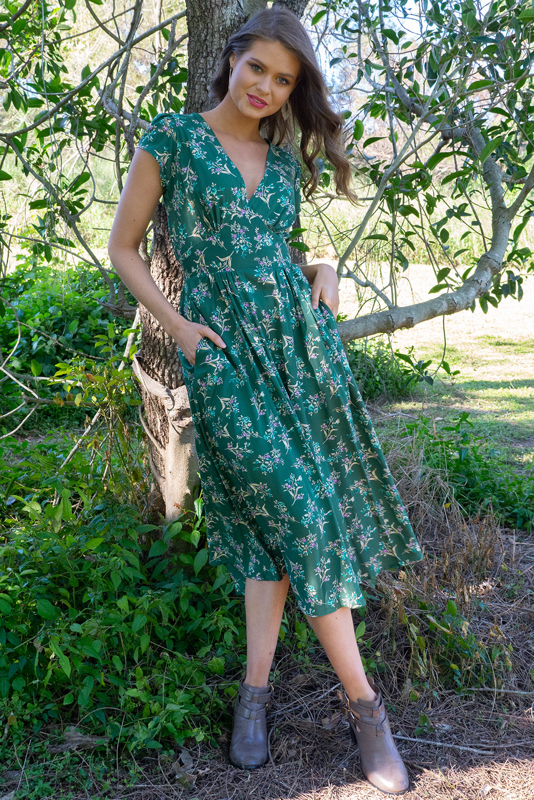 Lizzie Green Spring Midi dress features a vintage inspired fitted basque waist and elasticated waist with a cap sleeve and deep v neck the fabric is a soft woven rayon in a bright green floral print